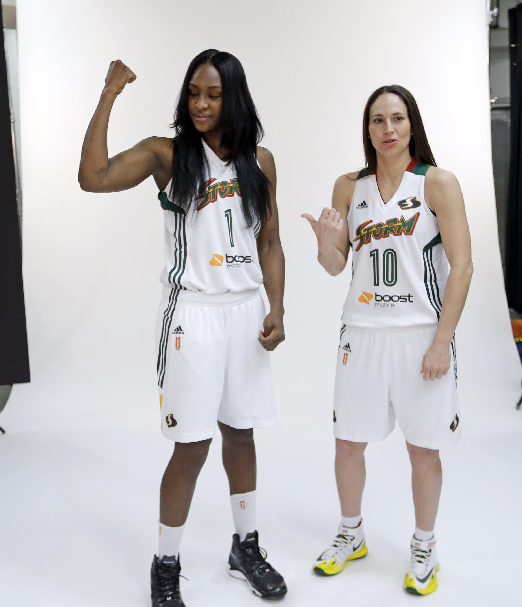 Seattle Storm's Crystal Langhorne, left, flexes her muscles after being asked as Sue Bird looks stands near during a photo session at the team's annual media day Wednesday, May 7, 2014, in Seattle. The team opens against the Los Angeles Sparks on May 16 in Seattle