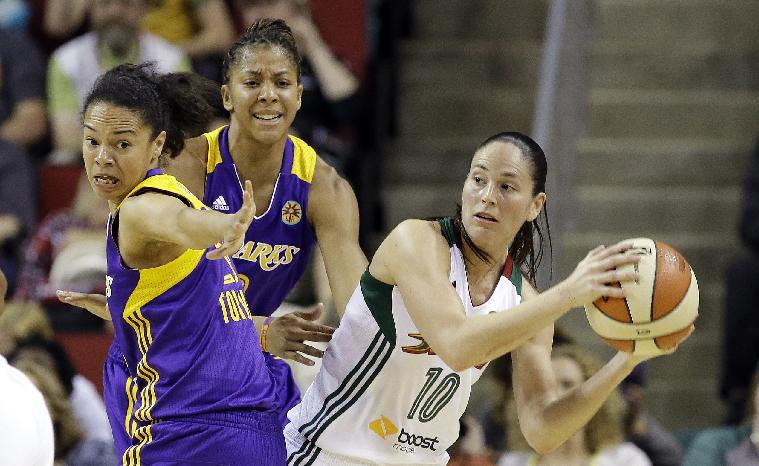 Seattle Storm's Sue Bird (10) is defended by Los Angeles Sparks' Kristi Toliver, left, and Candace Parker in the first half of a WNBA basketball game Friday, May 16, 2014, in Seattle