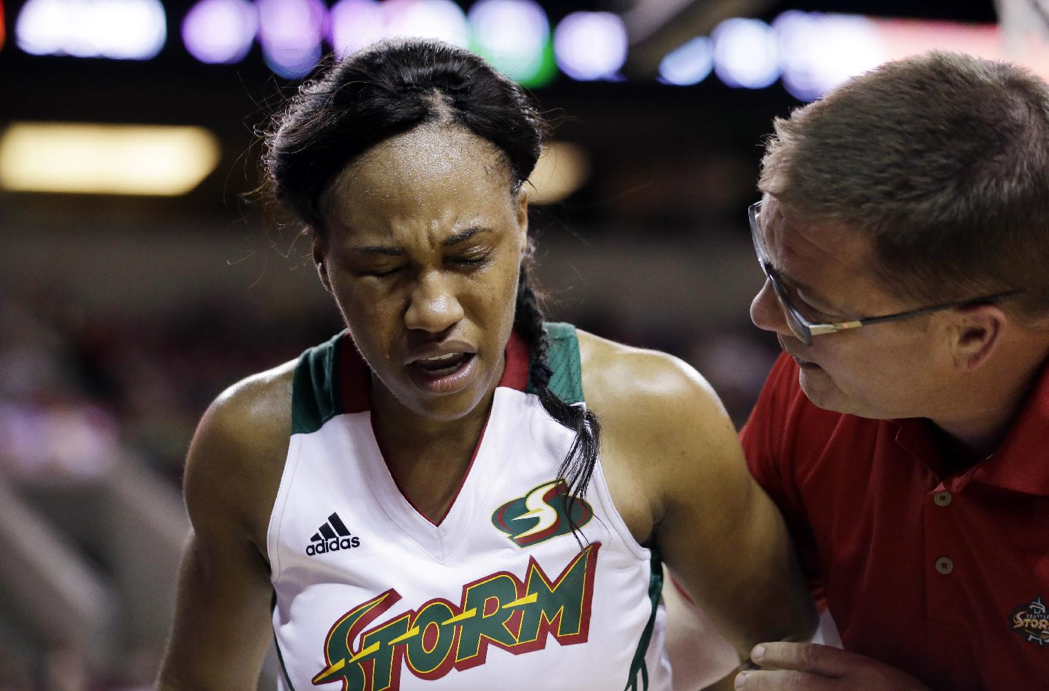 Seattle Storm's Temeka Johnson, left, is tended to by trainer Tom Spencer after being injured in the second half of a WNBA basketball game against the Los Angeles Sparks Friday, May 16, 2014, in Seattle. The Sparks won 80-69