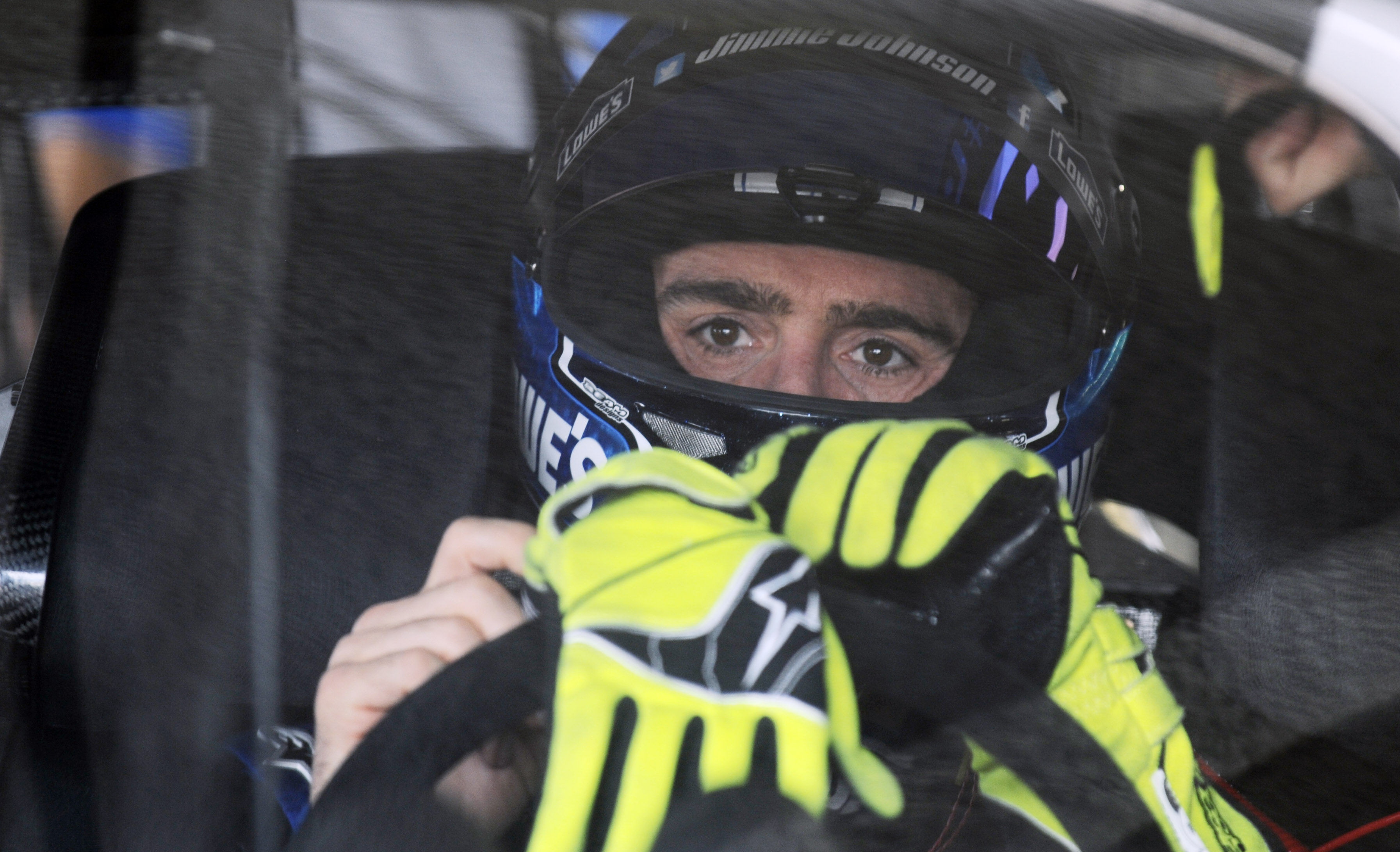 Jimmie Johnson puts on his gloves during practice for the Daytona 500. (USA TODAY Sports)