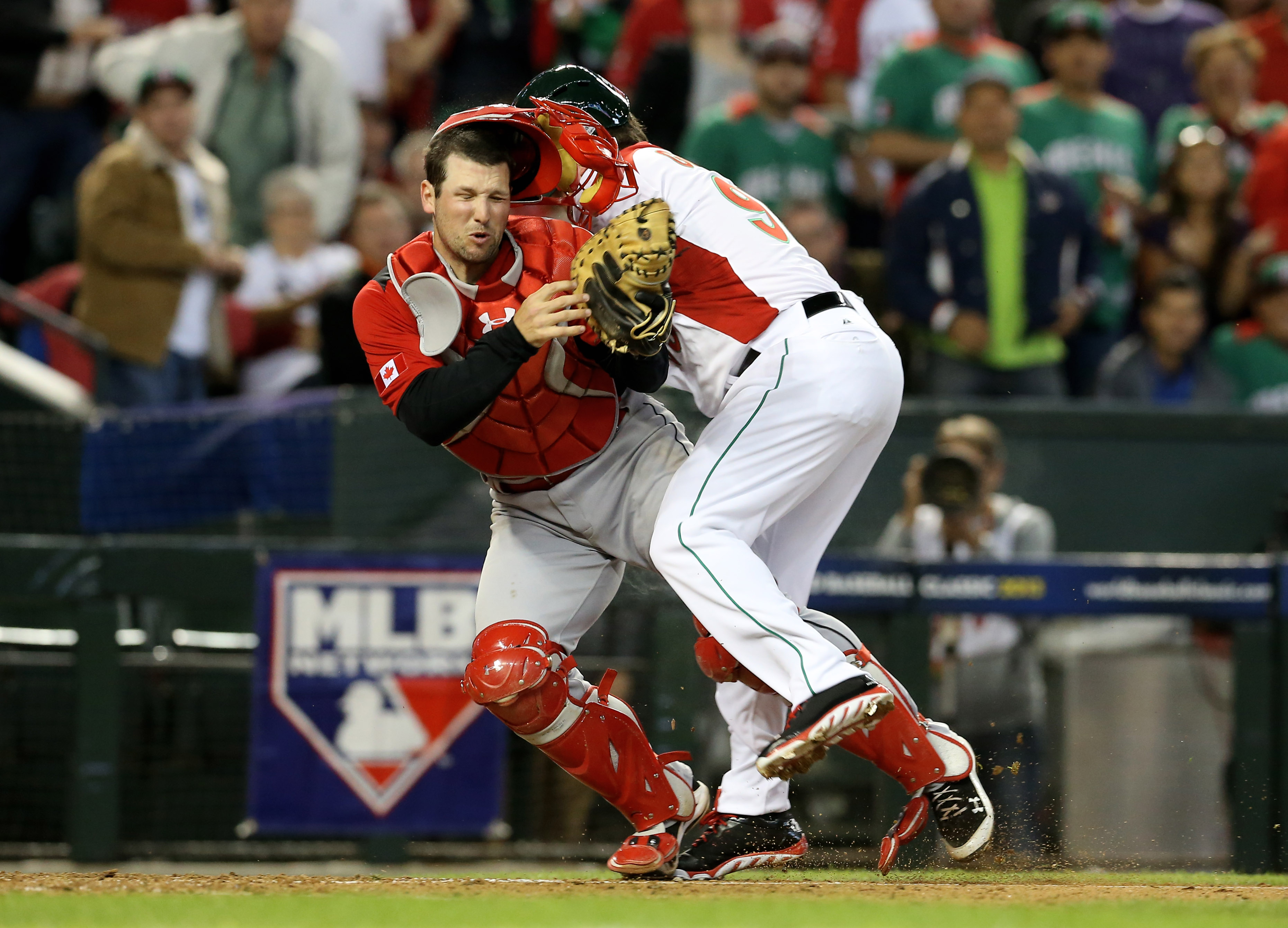 Mexico outfielder Karim Garcia collides with Canada catcher Chris Robinson in the fourth inning. (USA Today Sports)