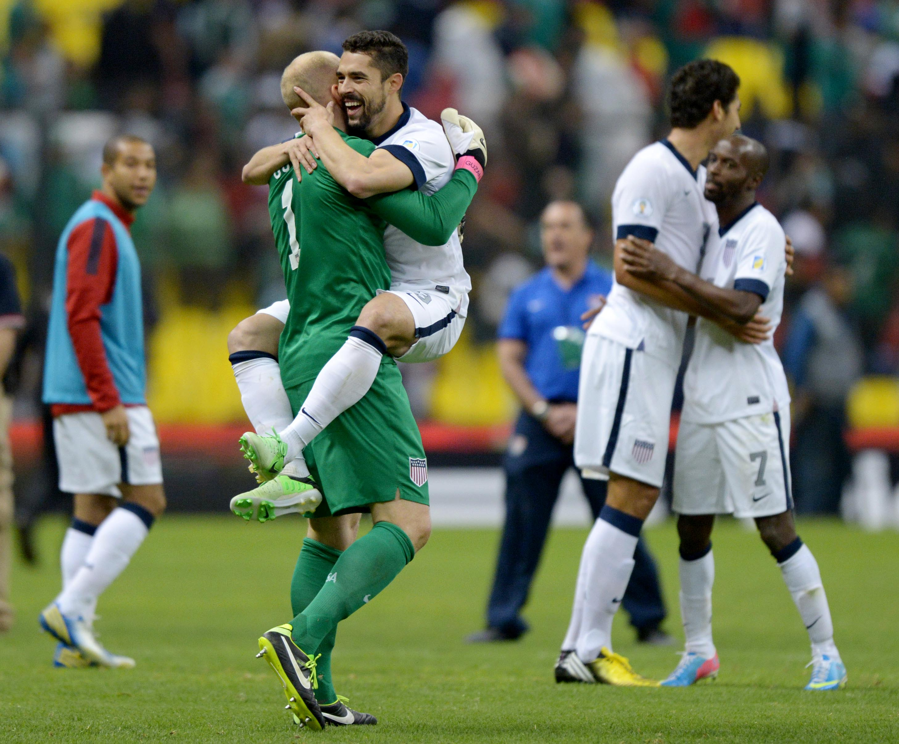 Brad Guzan (1) celebrates with Herculez Gomez after a 0-0 draw against Mexico. (USAT Sports)