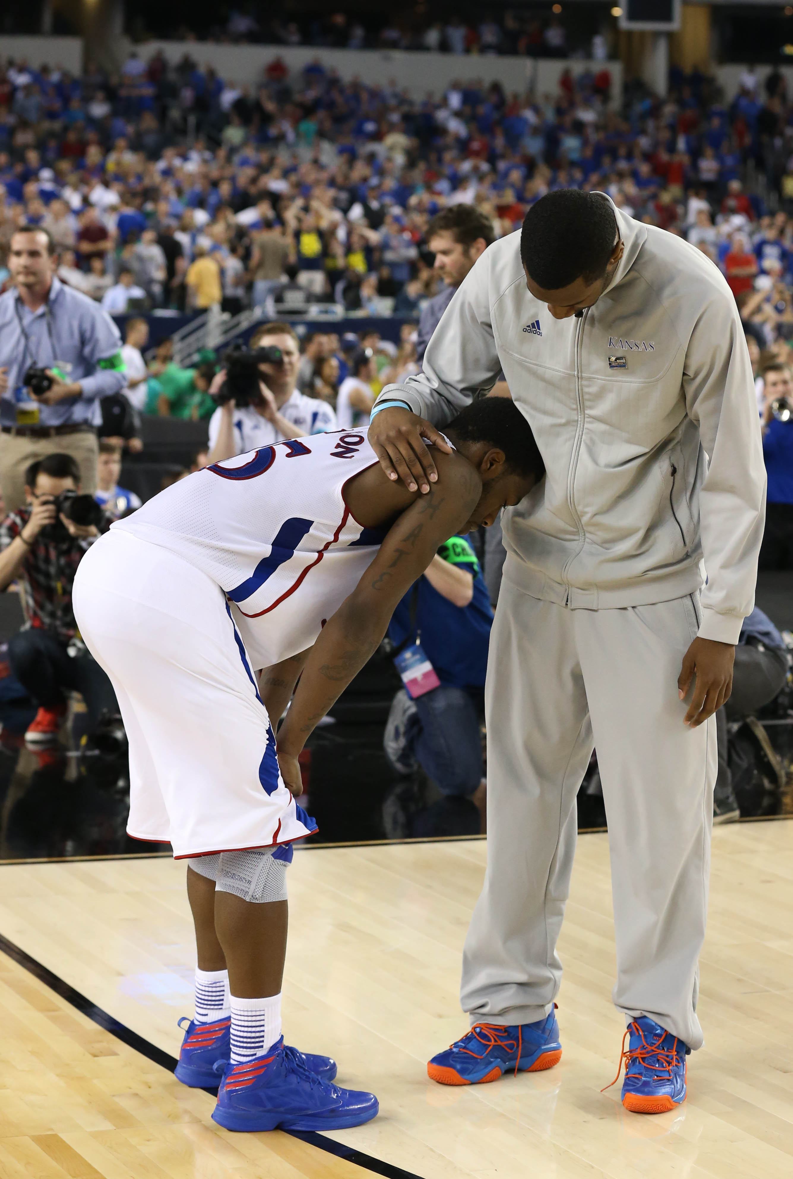 Jayhawks guard Elijah Johnson (L) reacts after losing to Michigan on Friday. (USA TODAY Sports)