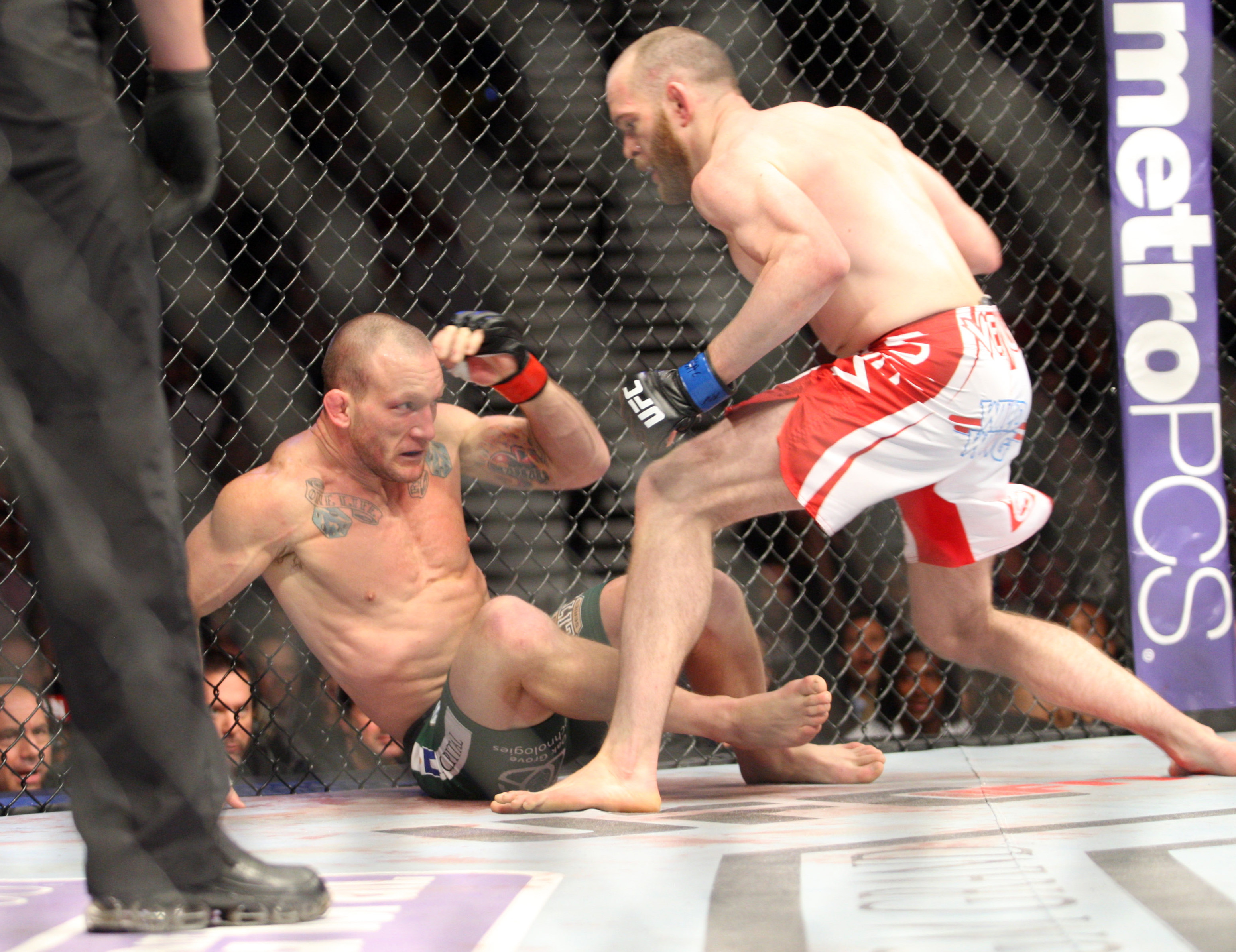 Gray Maynard lays against the cage as TJ Grant swarms in at UFC 160. (USA Today)