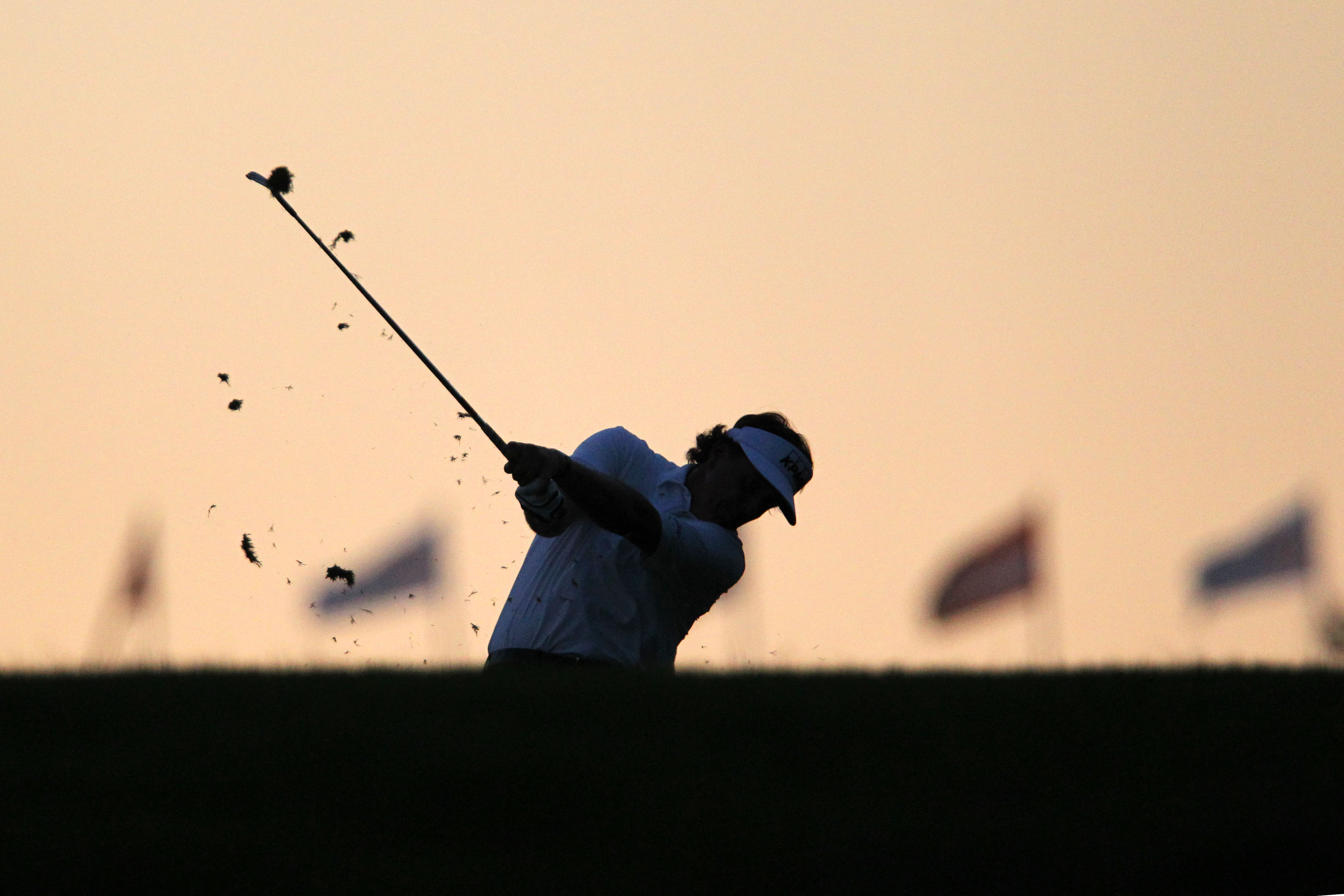 Phil Mickelson hits his second shot from the 18th fairway as darkness fell on Merion. (USA Today)