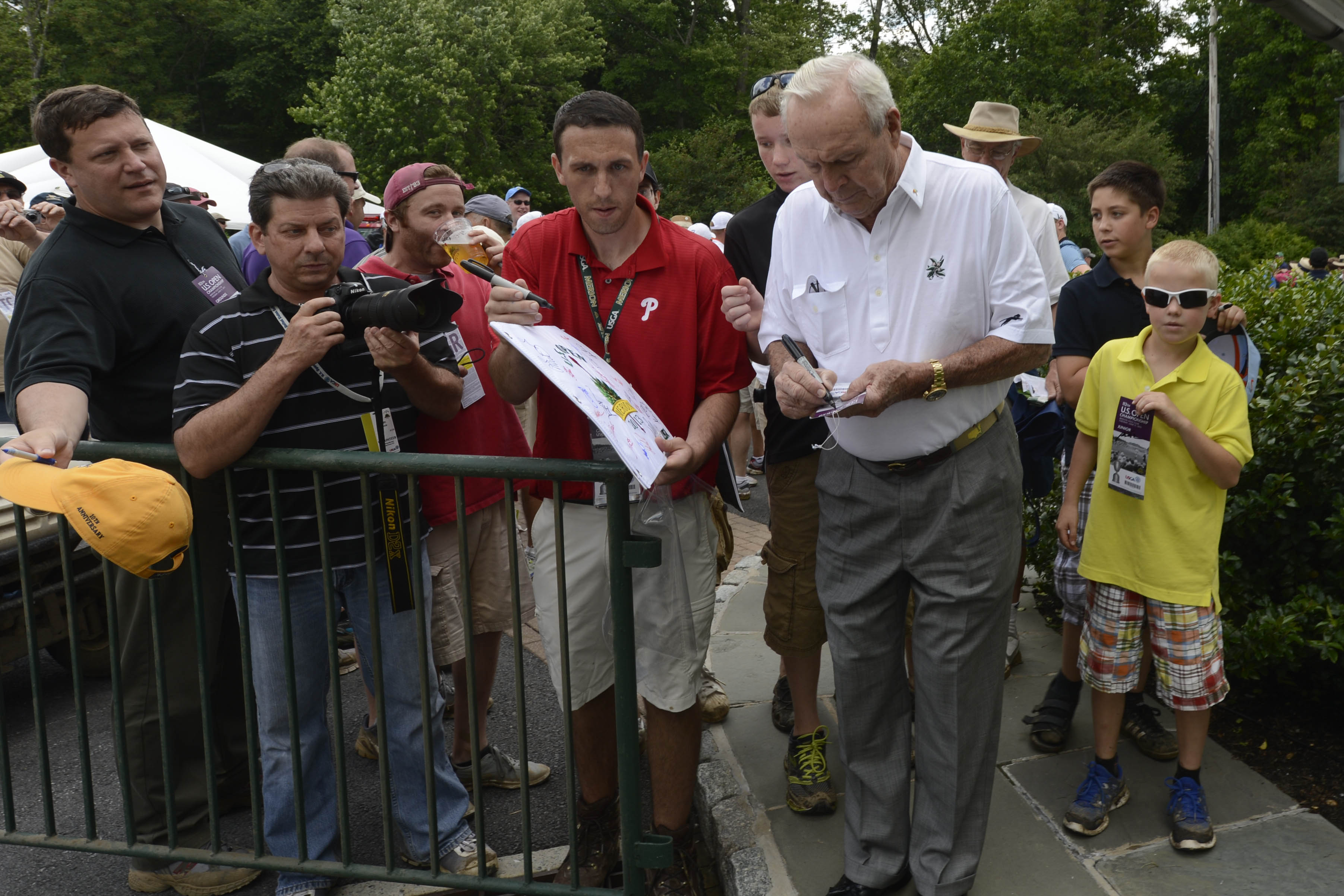 Jun 11, 2013; Ardmore, PA, USA; Arnold Palmer signs autographs for fans during the practice round of the 113th U.S. Open golf tournament at Merion Golf Club. (John David Mercer-USA TODAY Sports)