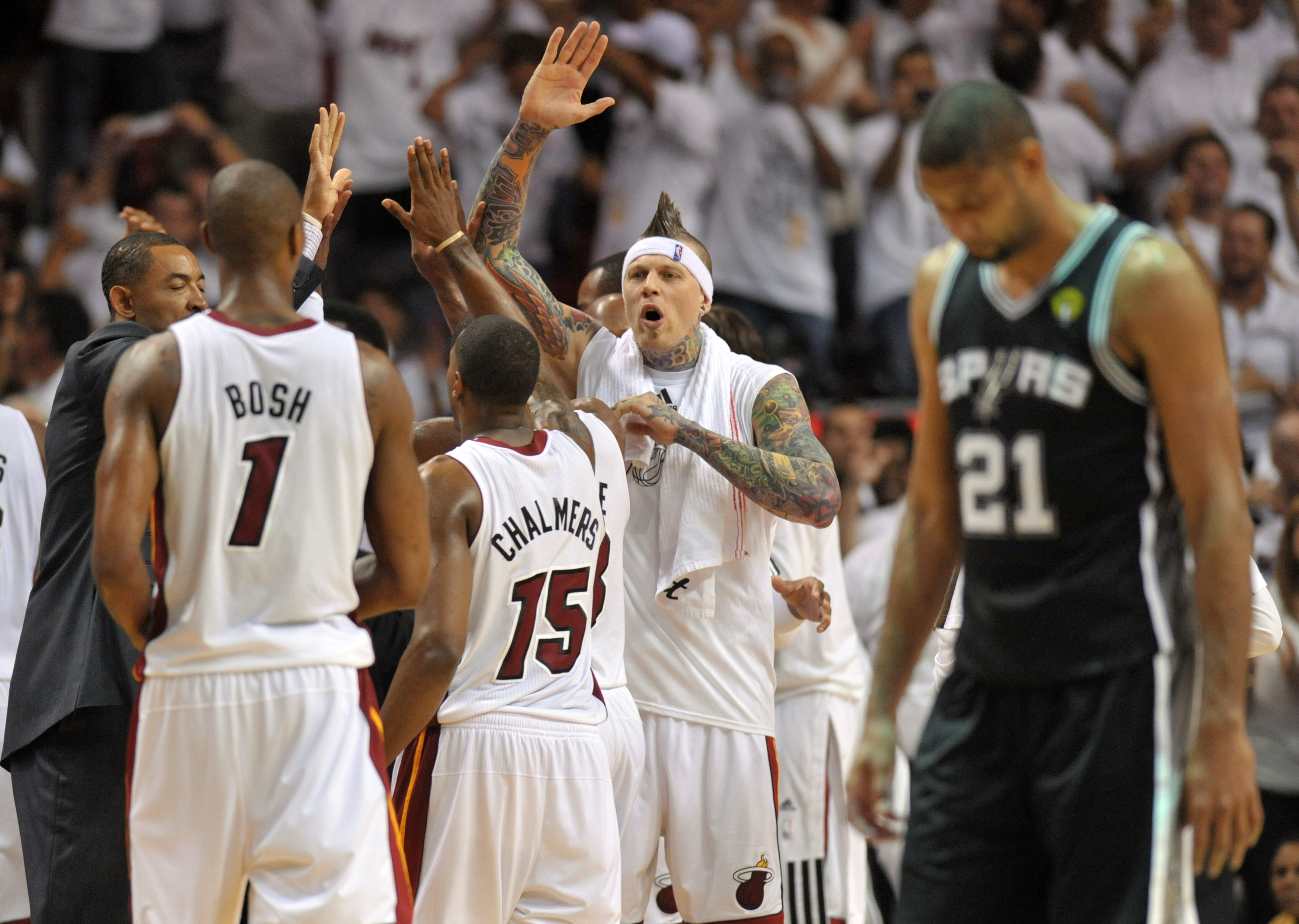 Tim Duncan walks off the court while the Heat celebrate. (USA TODAY Sports)