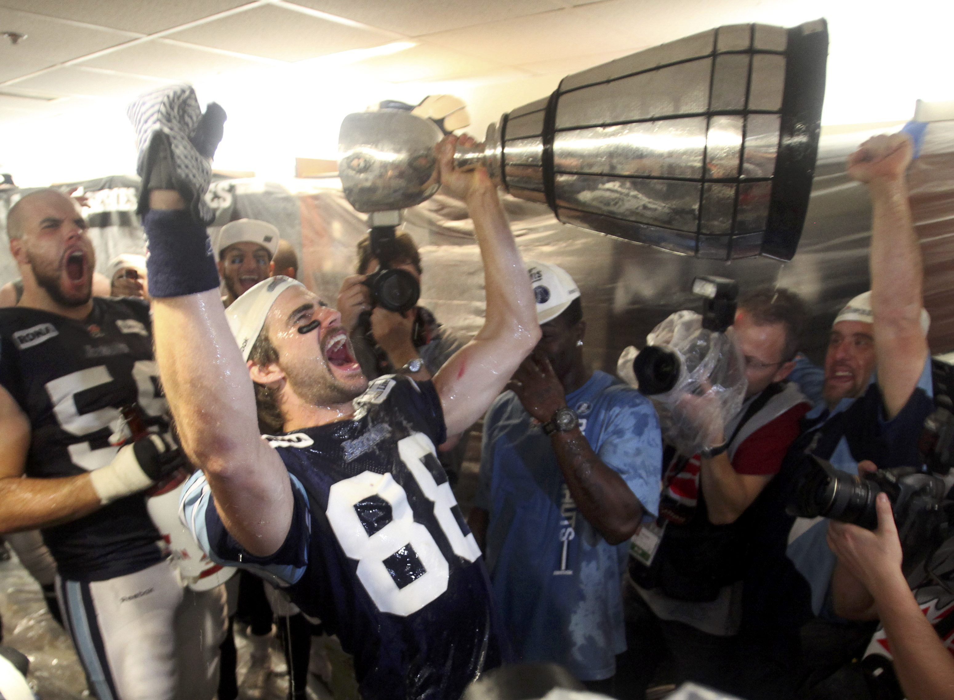 Argonauts receiver Mike Bradwell celebrates with the Grey Cup. (Reuters)