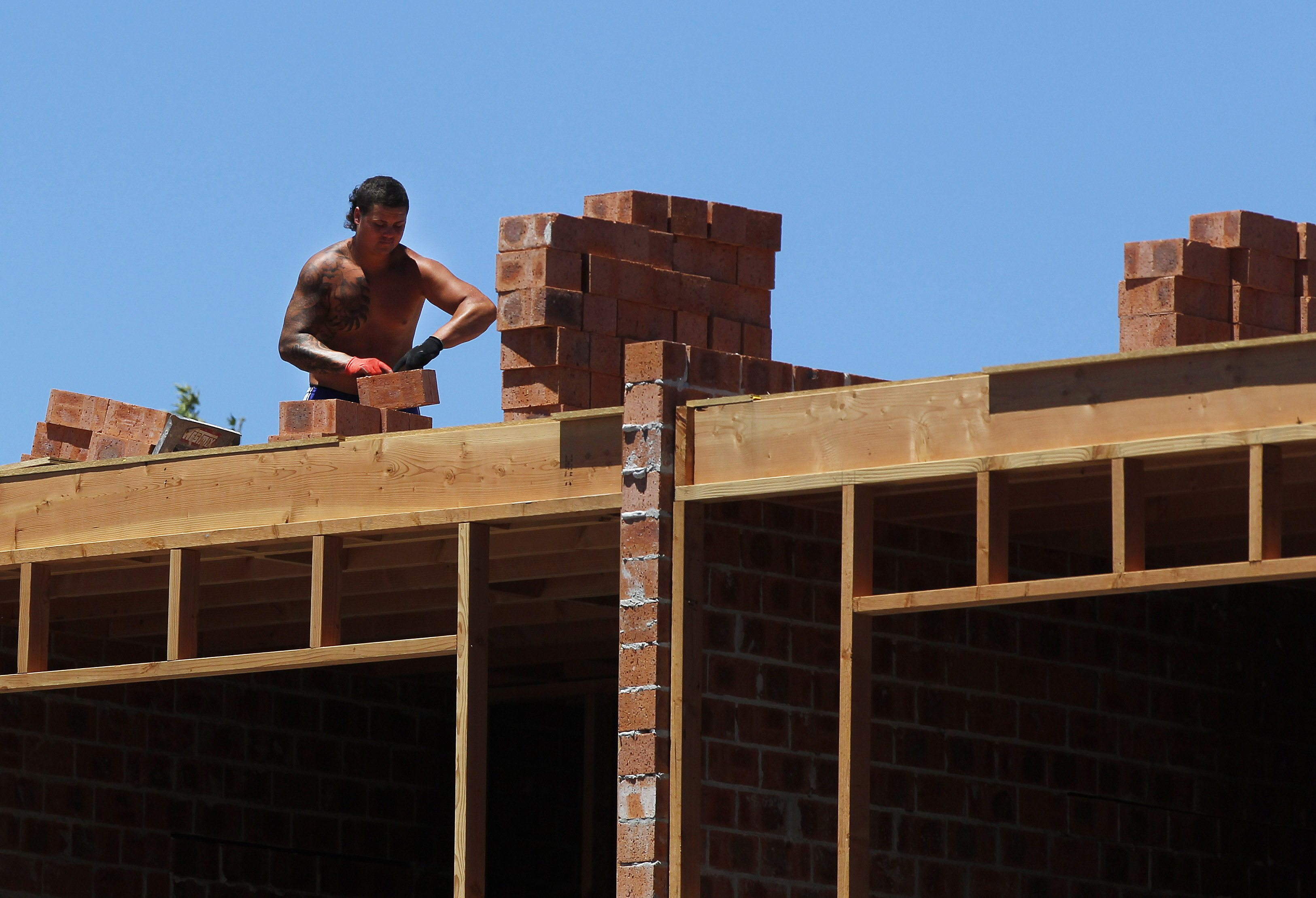 A worker carries bricks on top of a new apartment construction site. REUTERS/Daniel Munoz
