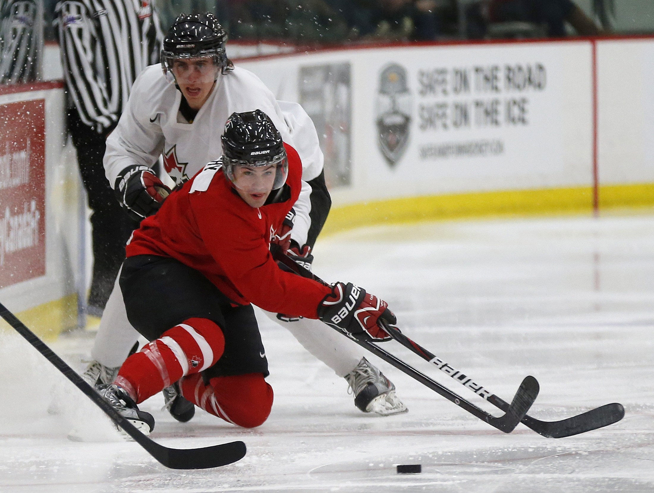 Team Canada's Ryan Murphy (R) is hauled down by CIS' Eric Galbraith during selection camp.