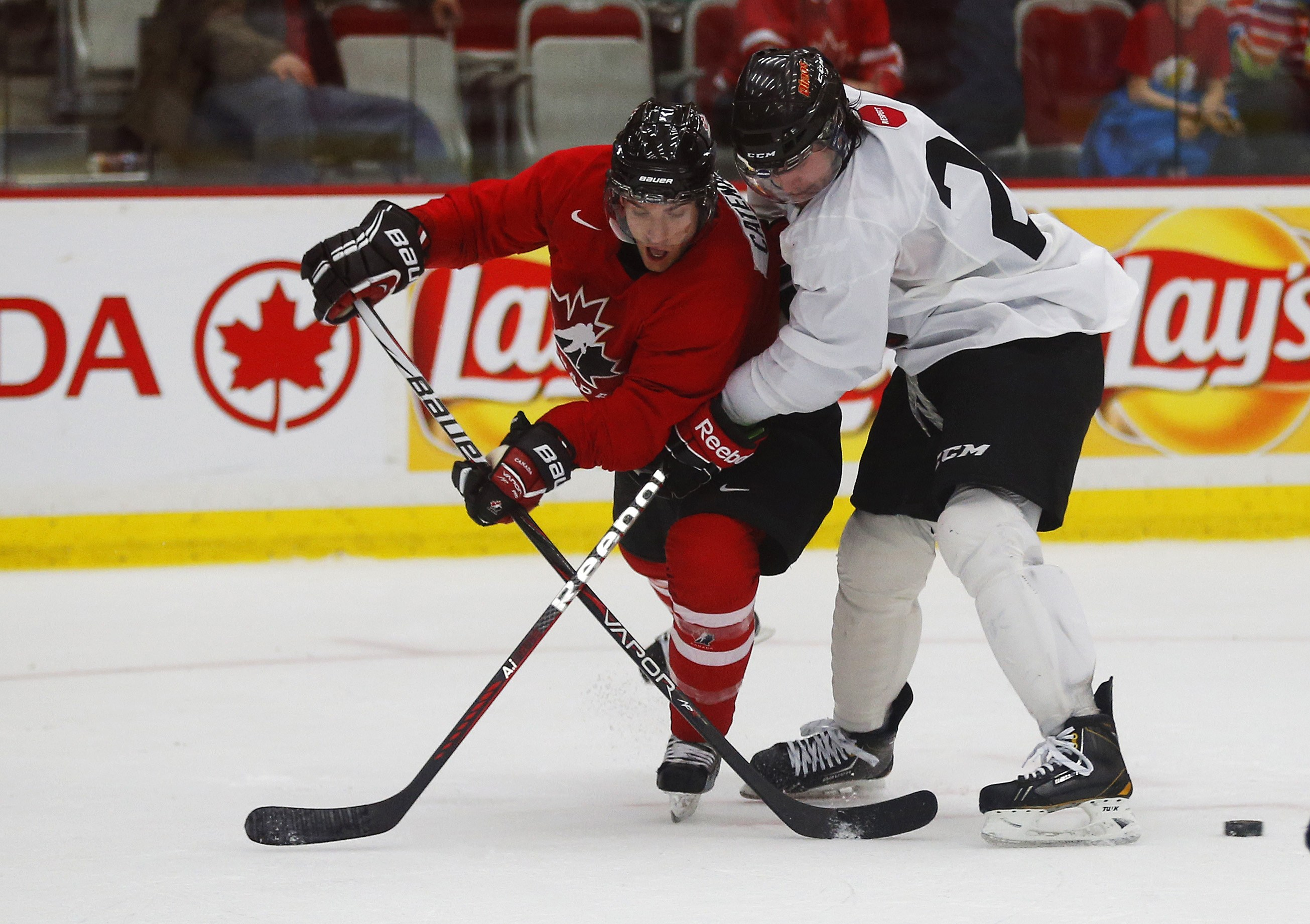 Team Canada's Daniel Catenacci (L) is stopped from taking a shot by CIS' Kodie Curran in selection camp.