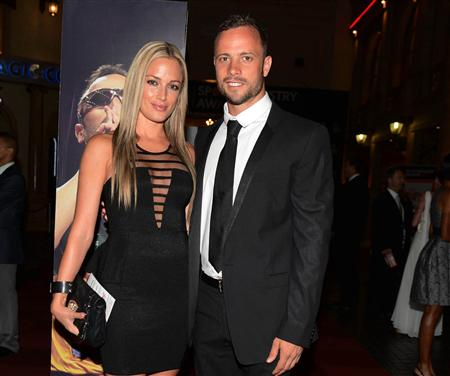 Oscar Pistorius (R) and his girlfriend Reeva Steenkamp pose for a picture in Johannesburg on February 7. (REUTERS)