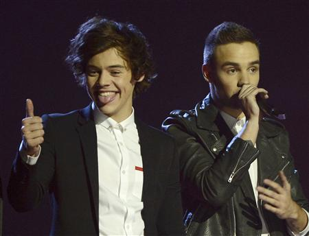 Singer Harry Styles (L) of Pop group One Direction reacts after being awarded the Global Success award at the BRIT Awards, celebrating British pop music, at the O2 Arena in London February 20, 2013. REUTERS/Dylan Martinez