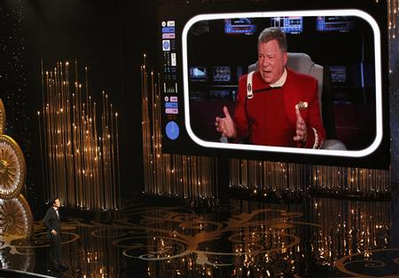 Oscar host Seth MacFarlane watches William Shatner on a screen during the opening segment of the 85th Academy Awards in Hollywood, California February 24, 2013. REUTERS/Mario Anzuoni