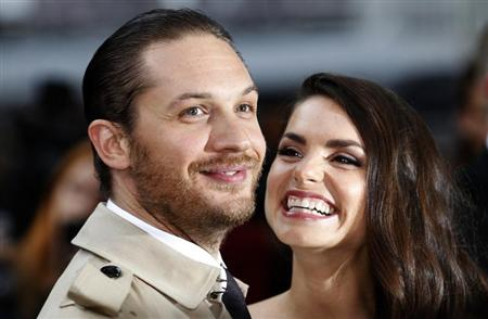 British actor Tom Hardy and his girlfriend Charlotte Riley pose for photographers as they arrive at the European Premiere of &quot;The Dark Knight Rises&quot; in Leicester Square, central London, July 18, 2012. REUTERS/Andrew Winning