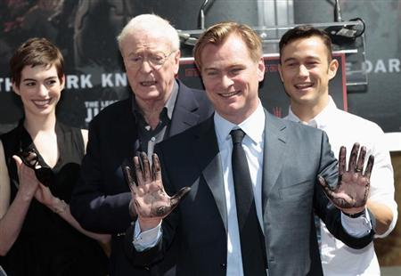 Director Christopher Nolan shows off his hands after leaving his handprints in cement during a hand and footprint ceremony in the forecourt of the Grauman's Chinese Theatre in Hollywood, California July 7, 2012. REUTERS/Mario Anzuoni