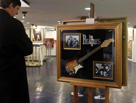 A visitor looks at a guitar signed by The Beatles at an exhibition in Buenos Aires, October 4, 2011. REUTERS/Enrique Marcarian