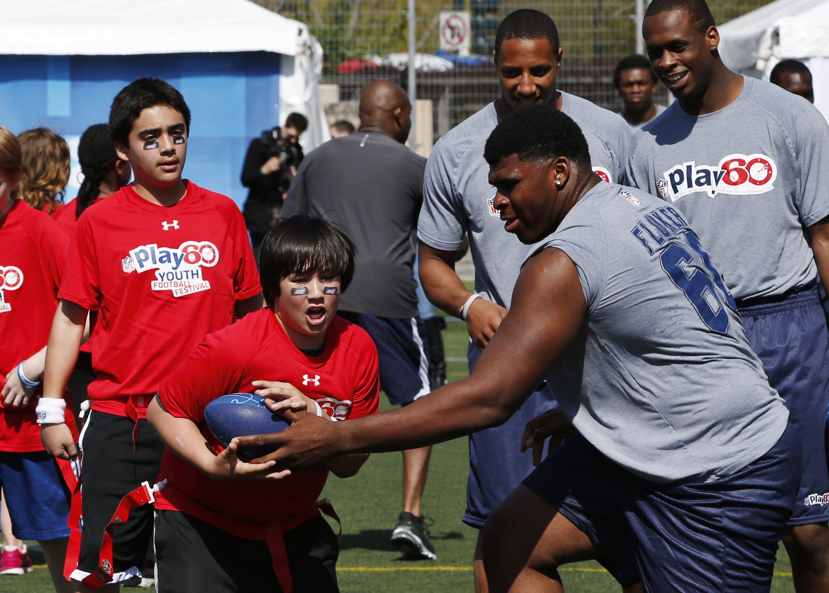 D.J. Fluker hands off to a boy as he takes part in an NFL Play 60 youth clinic. (Reuters)