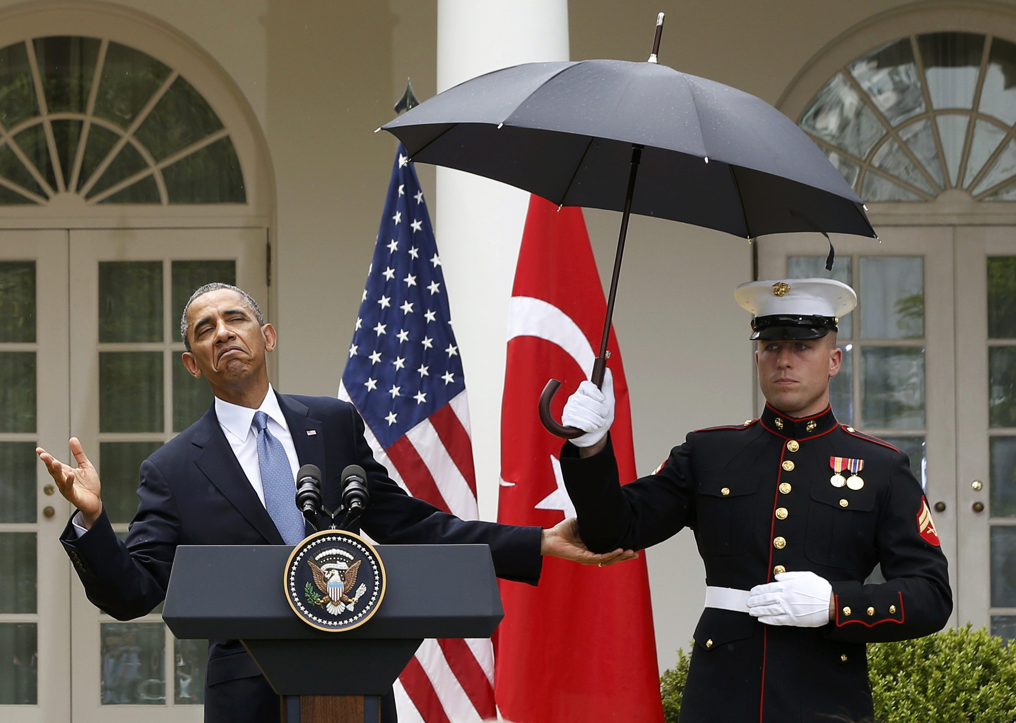 President Barack Obama decides he no longer needs umbrella help. (REUTERS/Jason Reed)