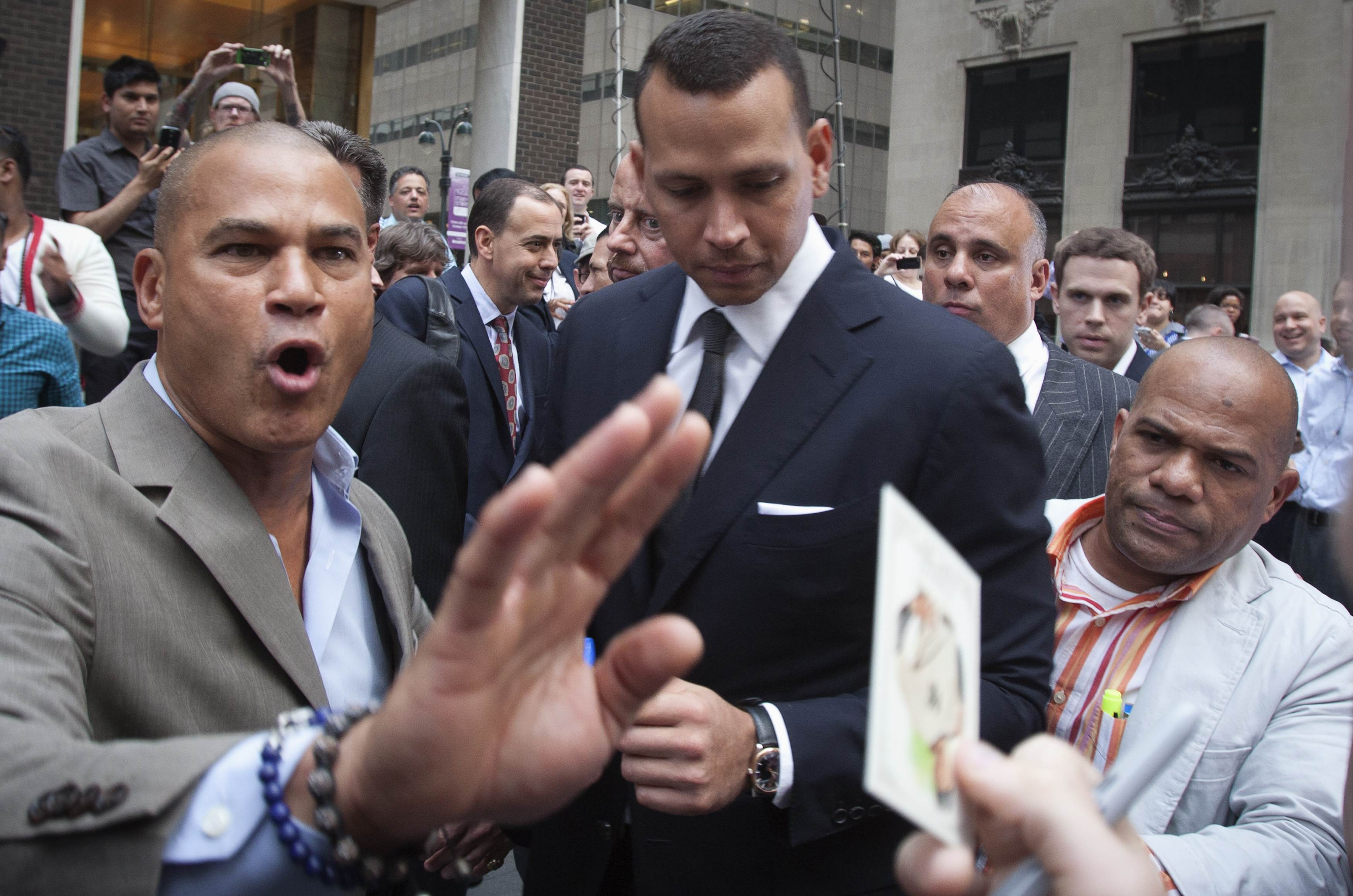 Alex Rodriguez (C) is surrounded by supporters