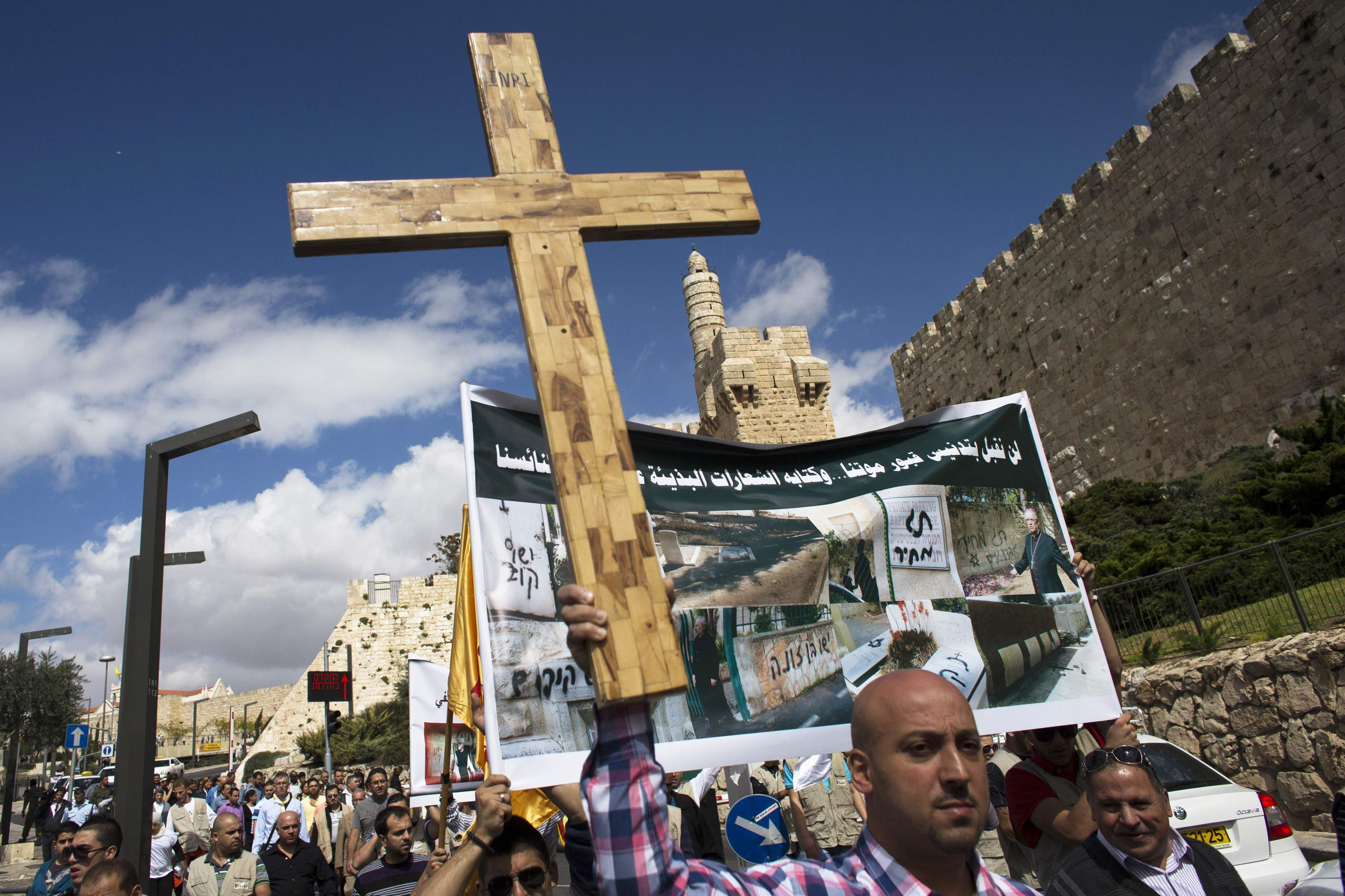 A Palestinian protester holds a cross during a demonstration against acts of vandalism on Christian sites in Israel and the occupied West Bank, outside Jerusalem's Old City
