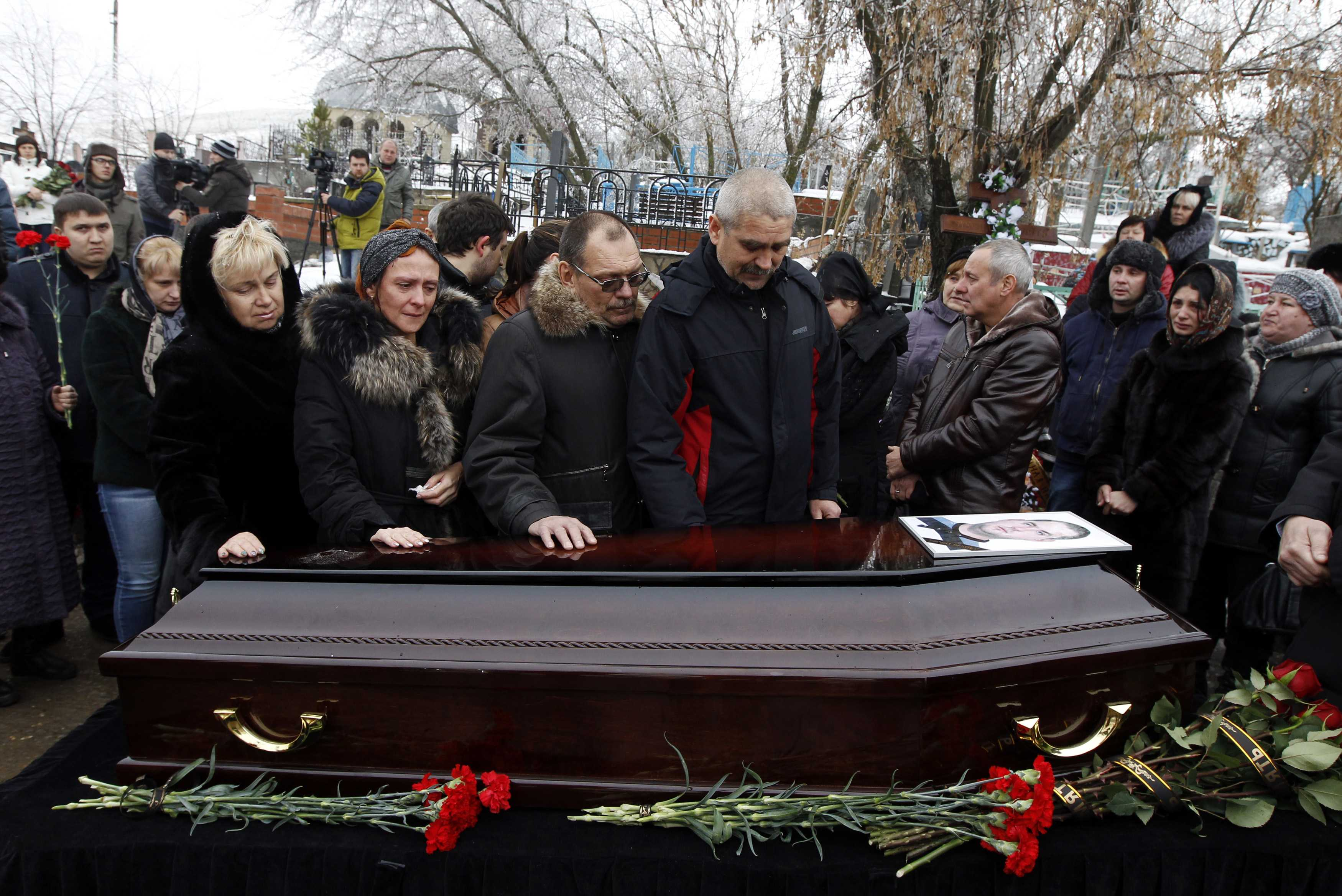 Relatives gather around the coffin of a victim of an explosion at a funeral in Volgograd