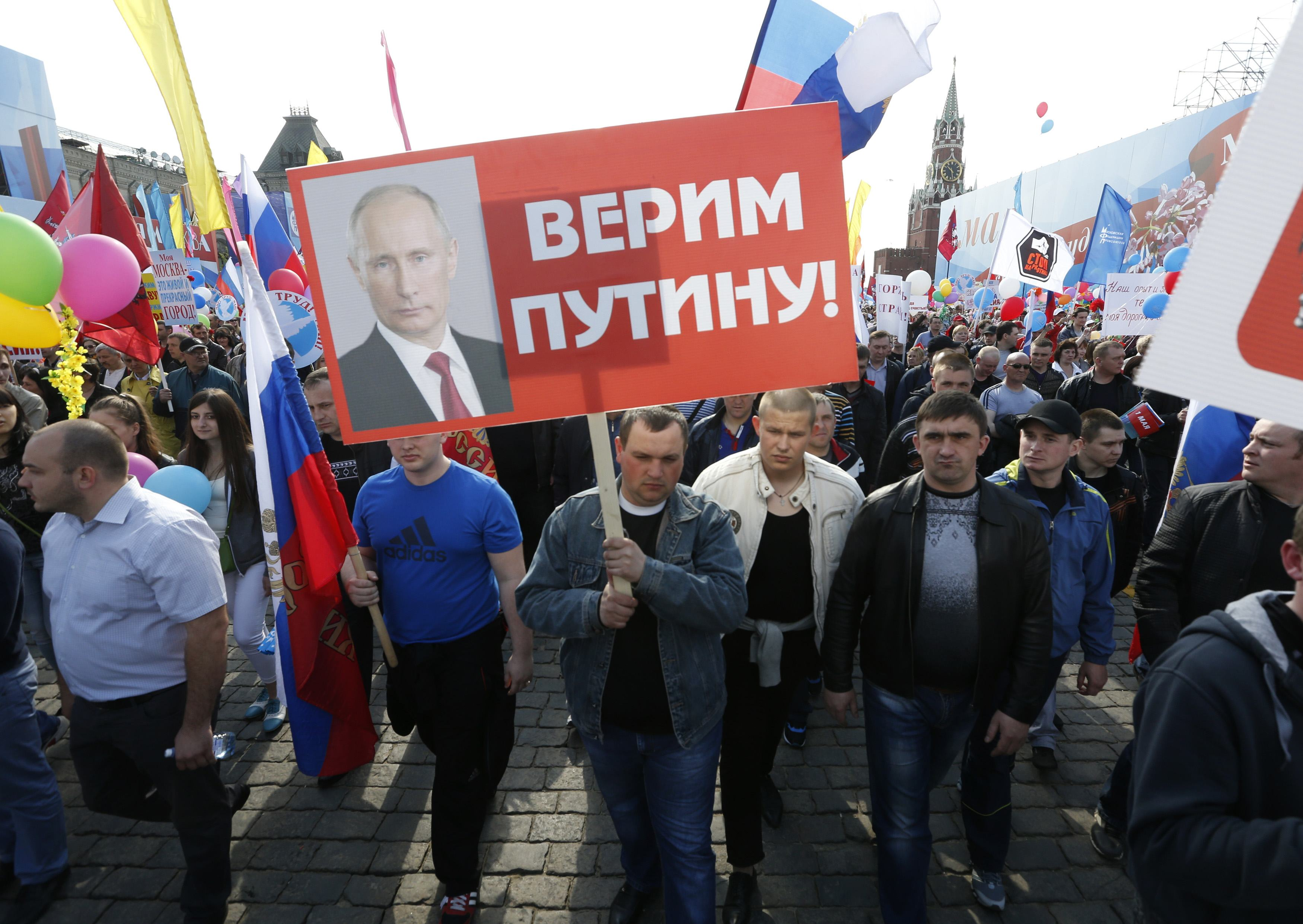 People walk through Red Square with flags and banners during a rally in Moscow
