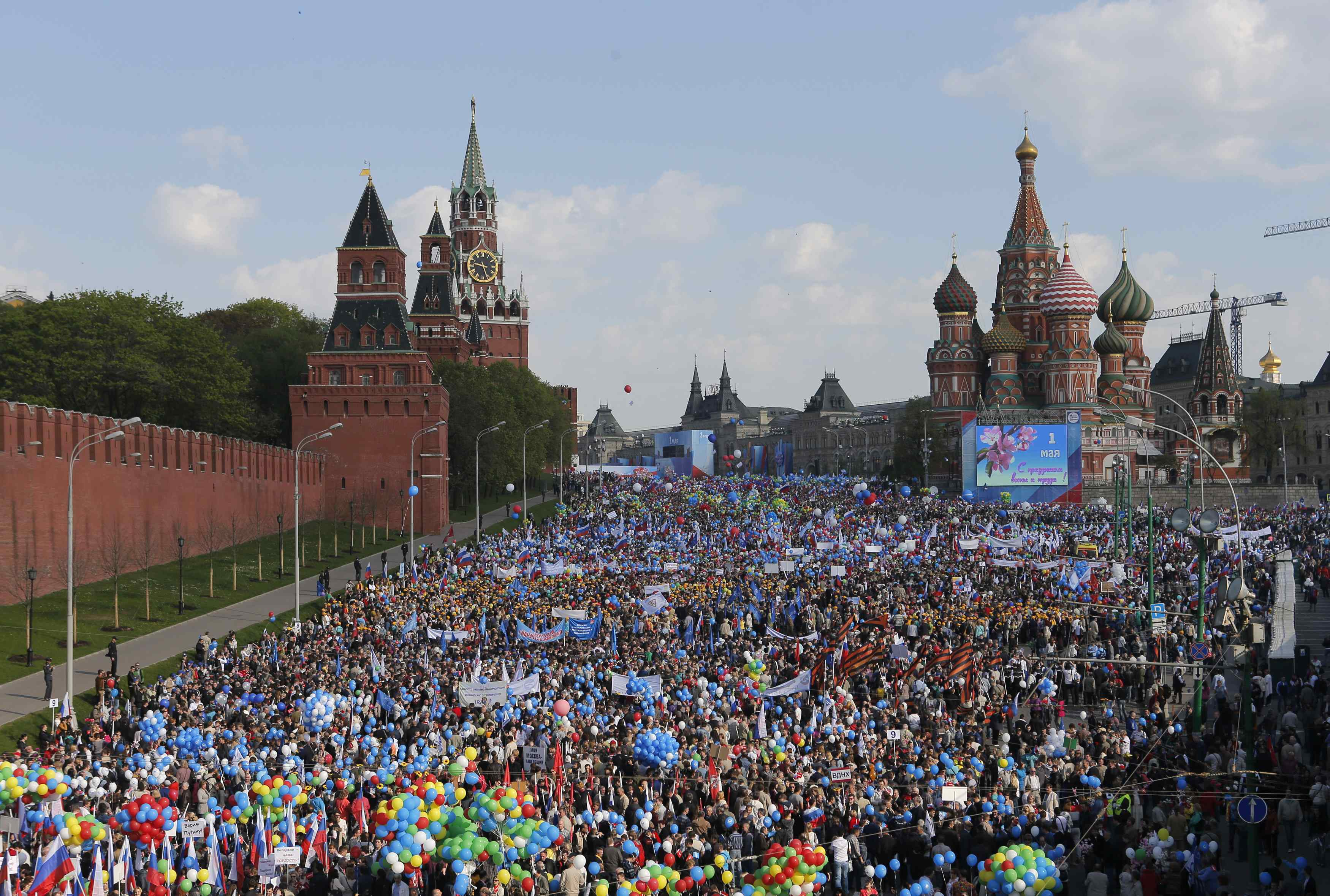 People walk with flags and balloons towards St. Basil's Cathedral on Red Square during a rally in Moscow