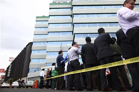 Workers evacuate a government building after a 6.8 magnitude earthquake in Mexico City