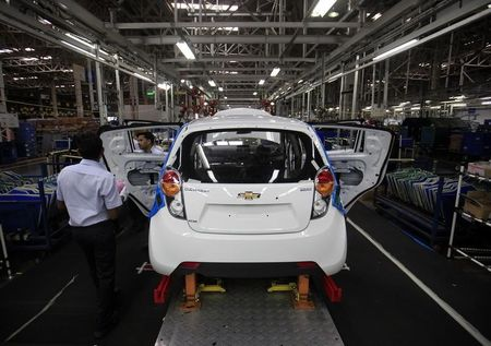employees work on a Chevrolet Beat car on an assembly line at the General Motors plant in Talegaon