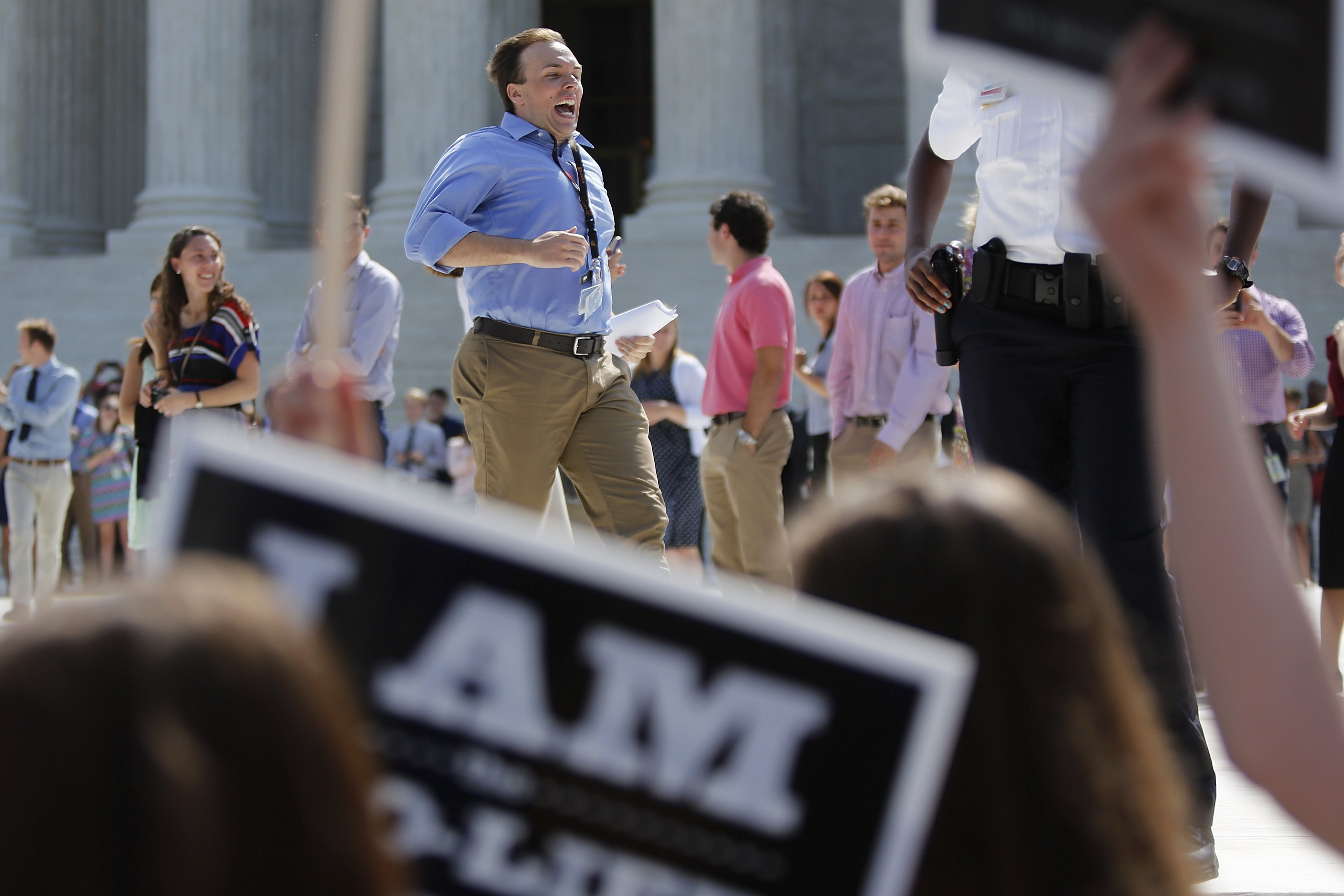 Reporters run from the courthouse with paper copies of the U.S. Supreme Court decision for the Hobby Lobby, in Washington