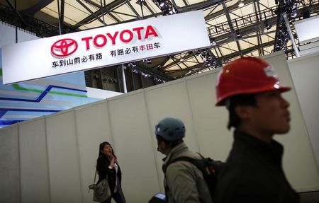 A worker walks in front the Toyota Motor Corp stage prior to the opening of the 15th Shanghai International Automobile Industry Exhibition in Shanghai