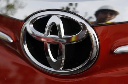 Worker is reflected next to the emblem of a Toyota Vios sedan at a stockyard of the Toyota Philippines manufacturing plant in Sta Rosa, Laguna, south of Manila