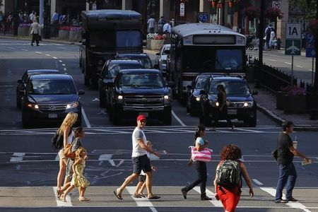 Pedestrians cross the street as cars wait at an intersection in Boston