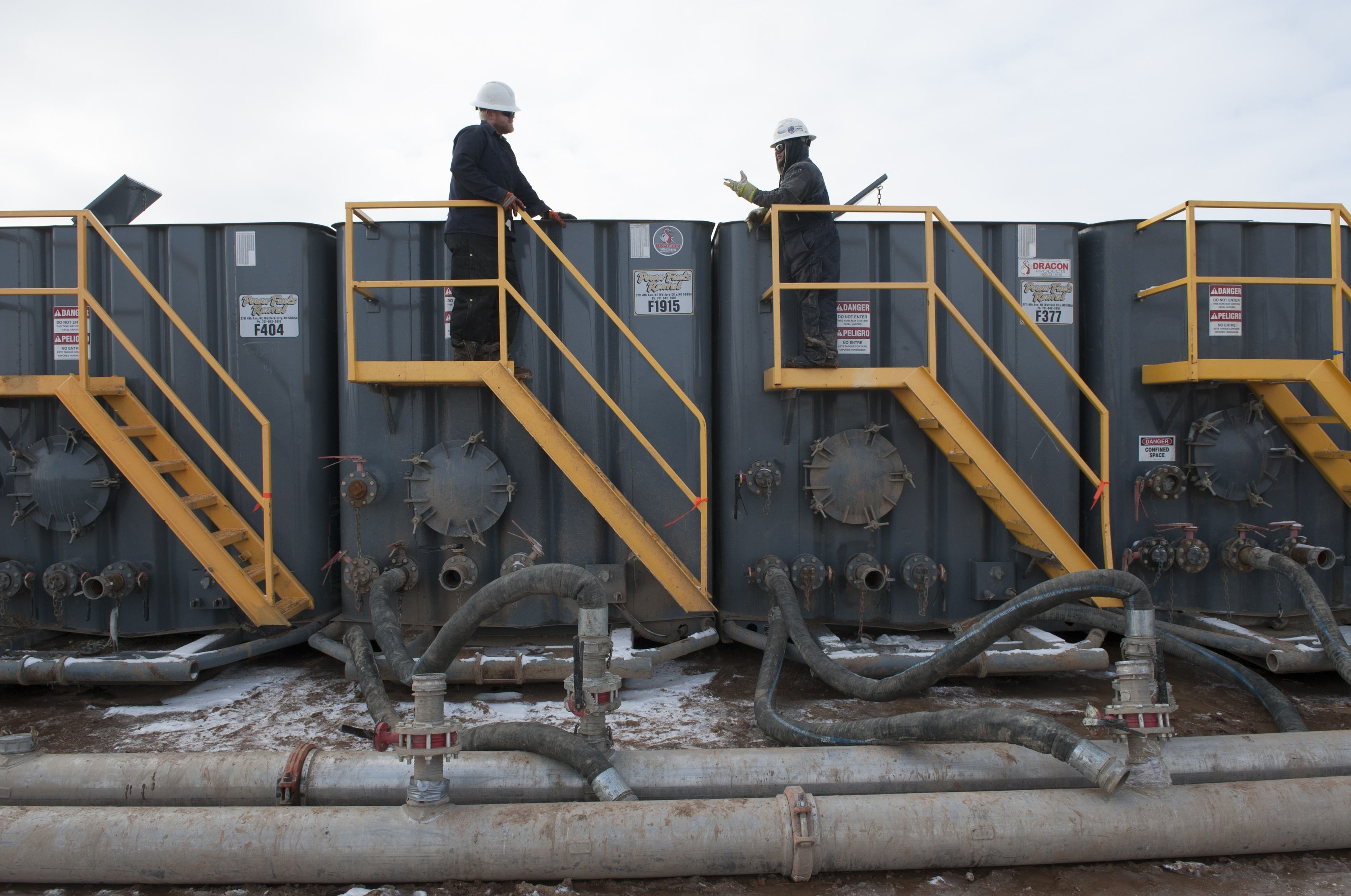 A worker monitors water tanks at a Hess fracking site near Williston
