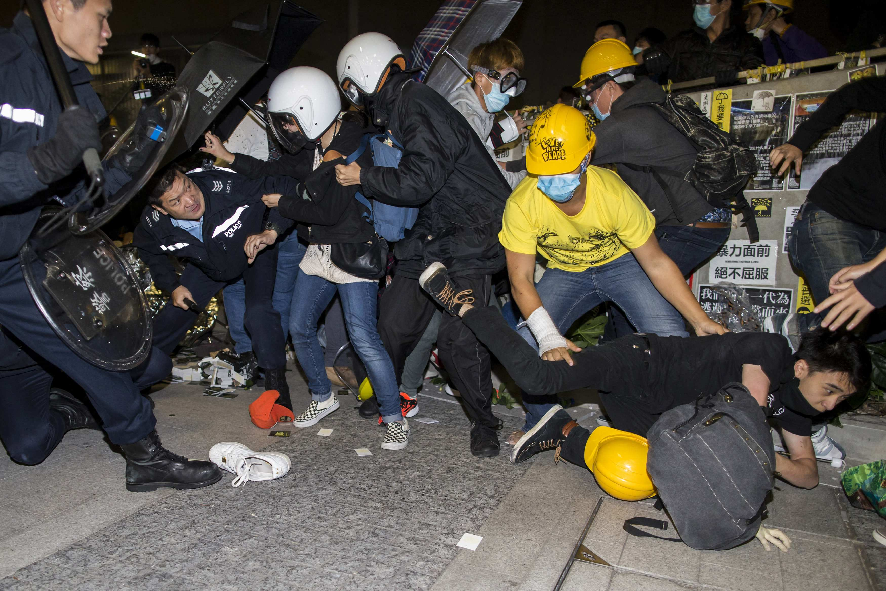 A protester falls on the ground as they are chased by riot police outside the Legislative Council in Hong Kong early