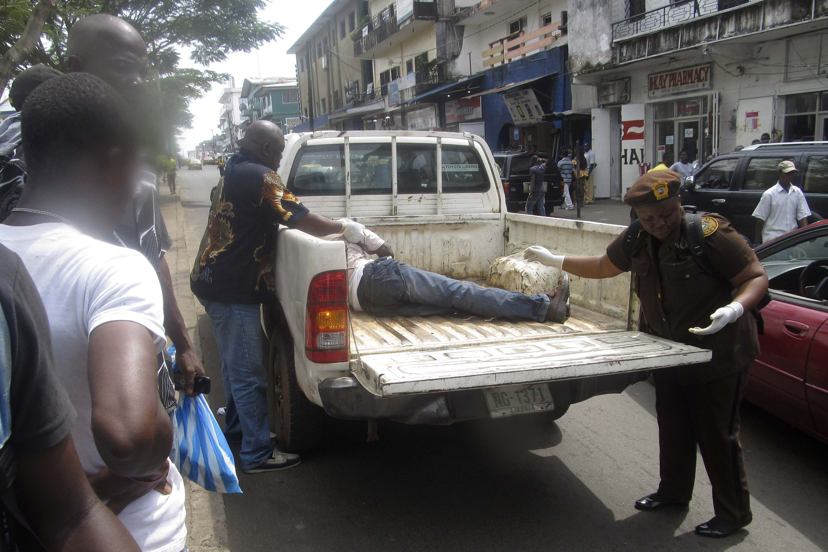 A man is carried away to be tested for Ebola after collapsing on a street in Monrovia