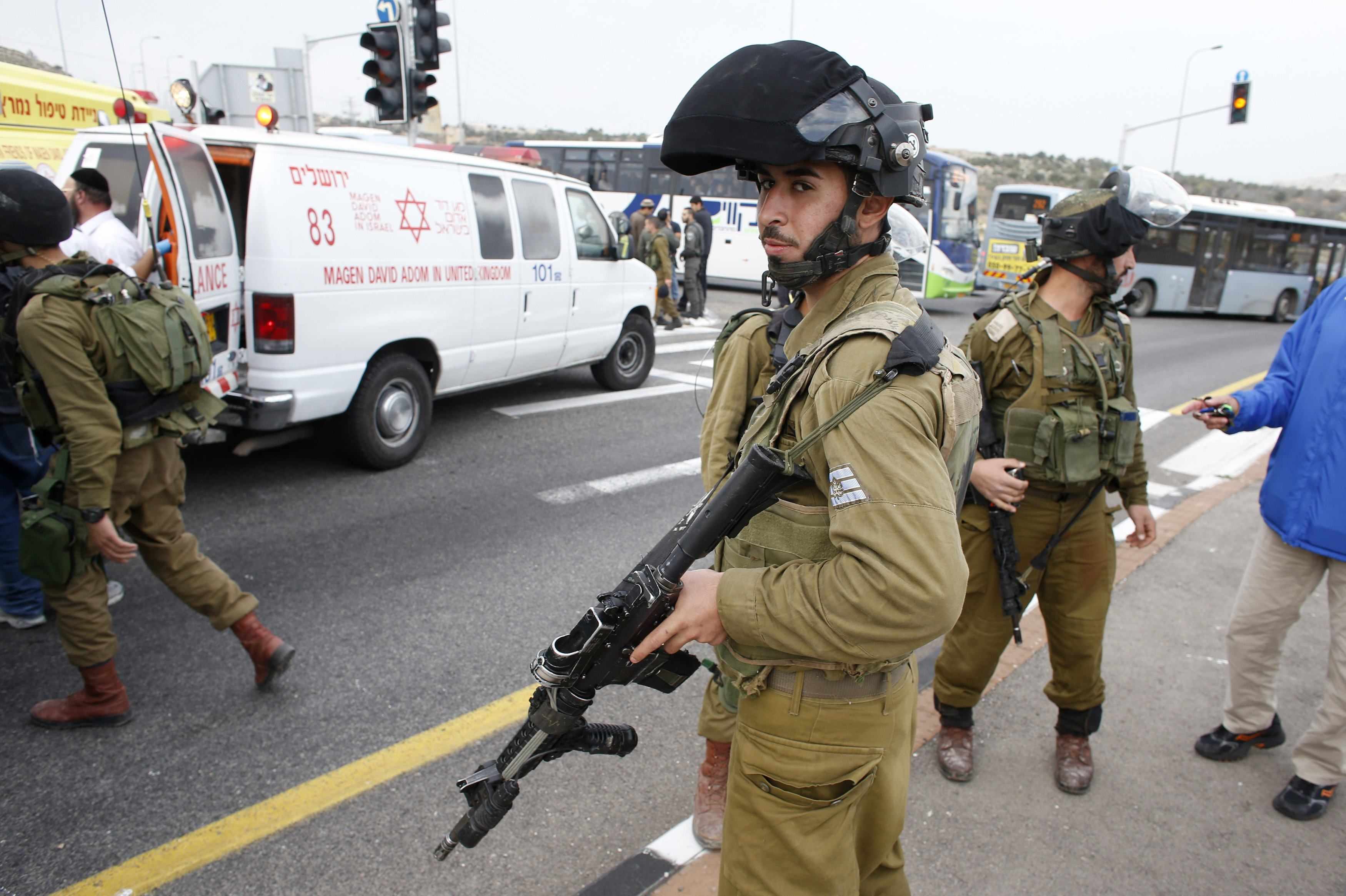 An Israeli soldier stand at the scene where a Palestinian attacked civilians with a chemical substance near the West Bank Jewish settlement of Neve Daniel