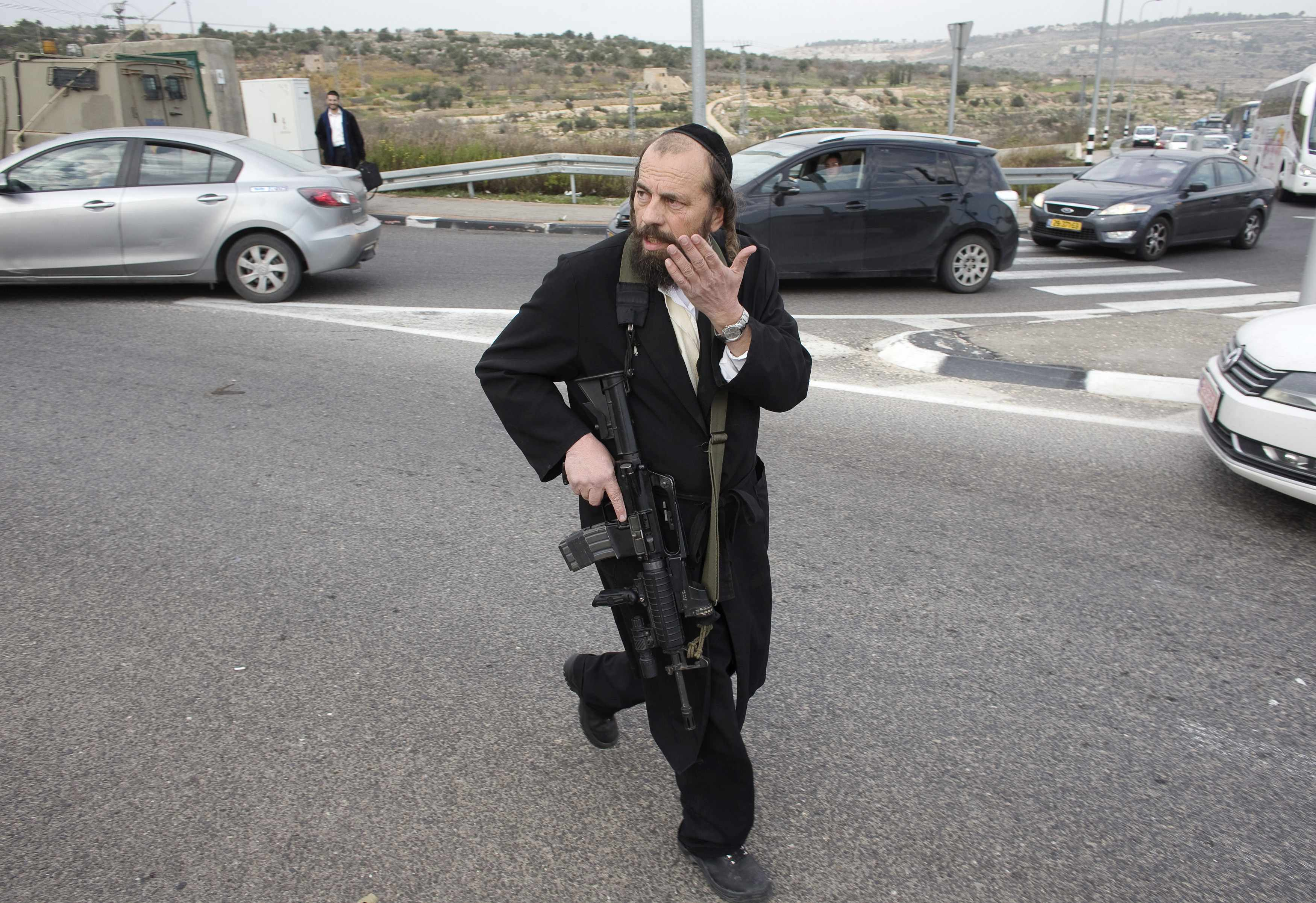 An Israeli Ultra-Orthodox Jewish man run at the scene where a Palestinian attacked civilians with a chemical substance near the West Bank Jewish settlement of Neve Daniel