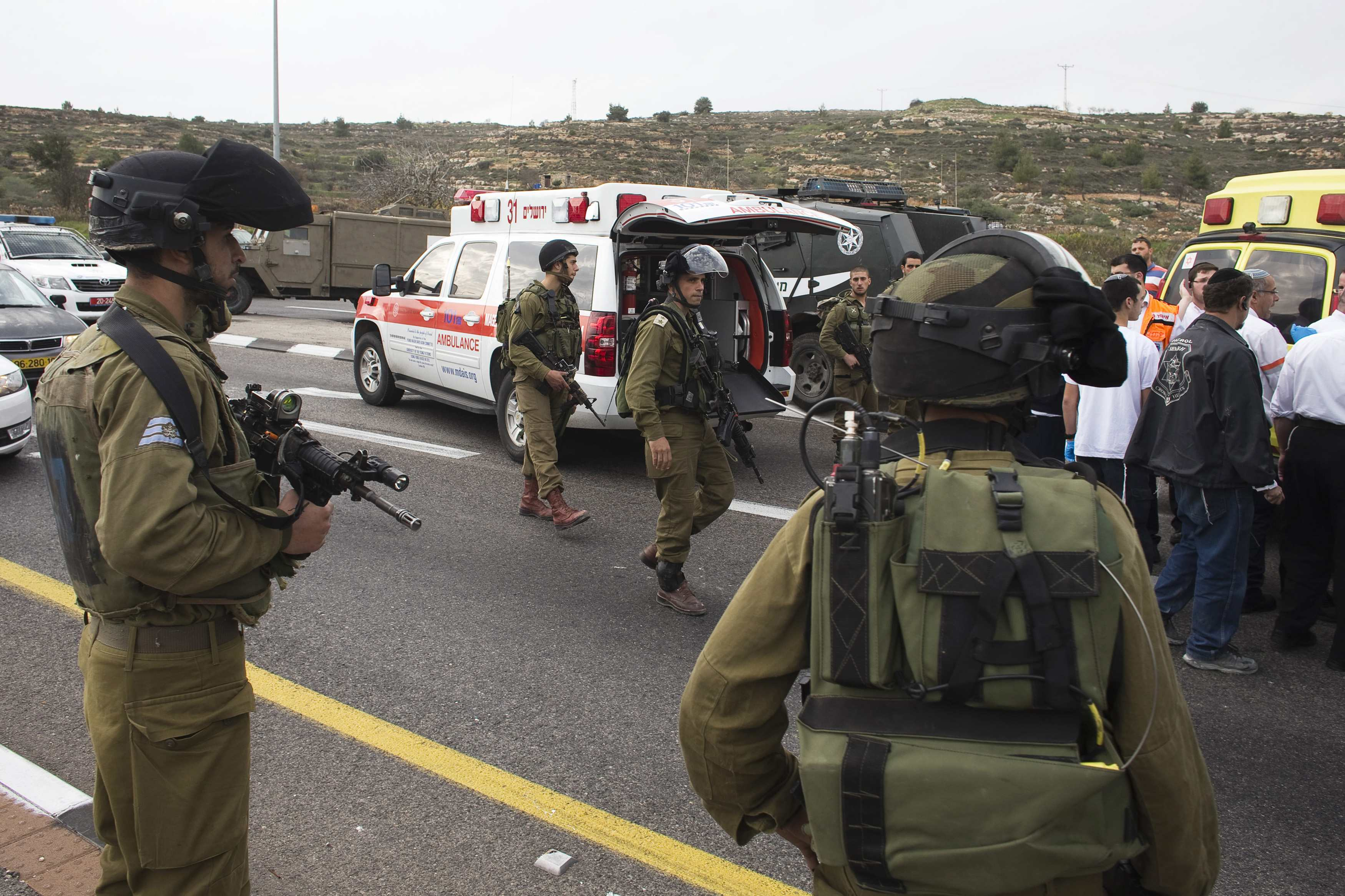 An Israeli soldiers stand as medics evacuate an injured girl from the scene where a Palestinian attacked civilians with a chemical substance near the West Bank Jewish settlement of Neve Daniel