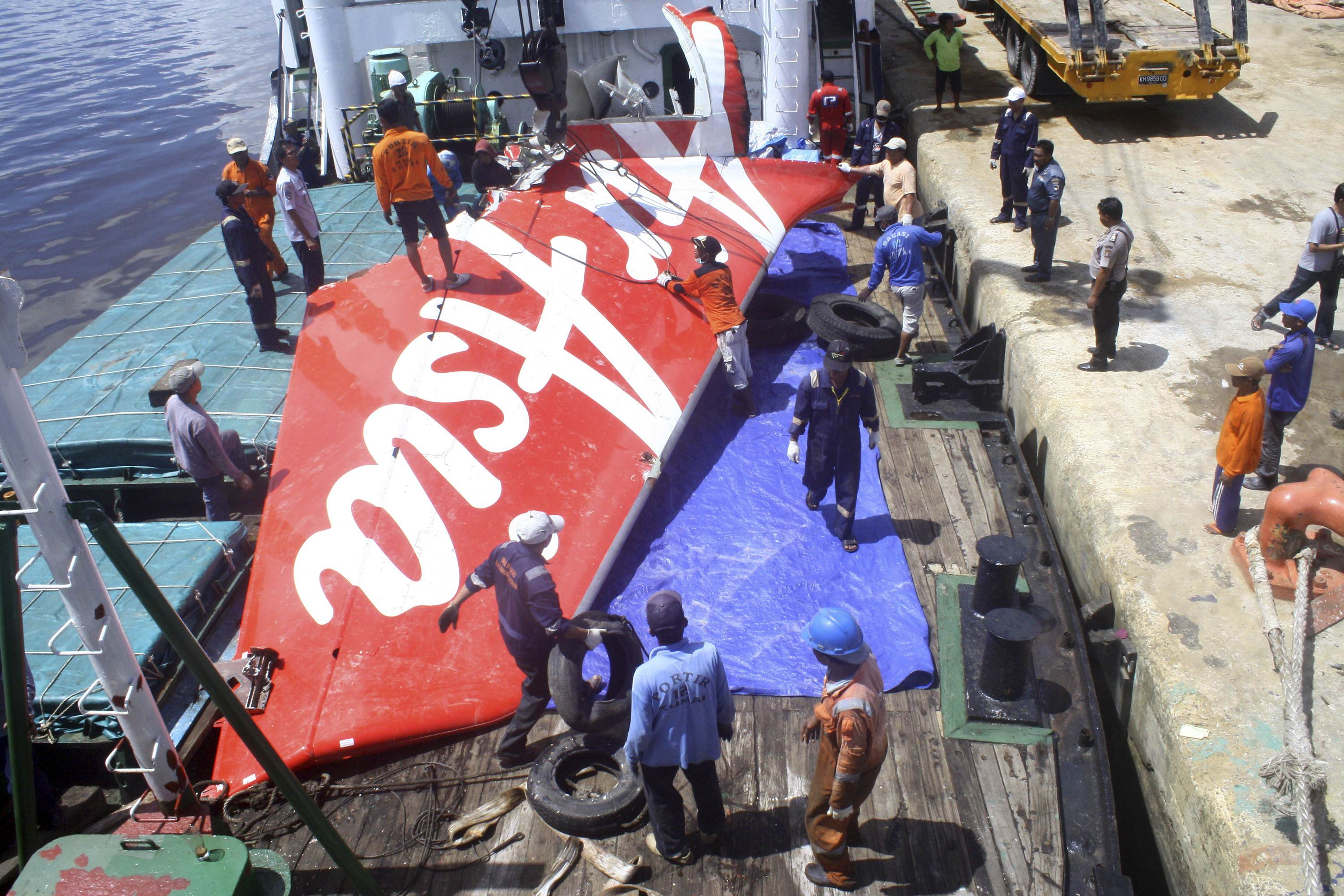 A section of AirAsia flight QZ8501's tail is loaded onto a boat for transportation to Jakarta from Kumai Port, near Pangkalan Bun, Central Kalimantan