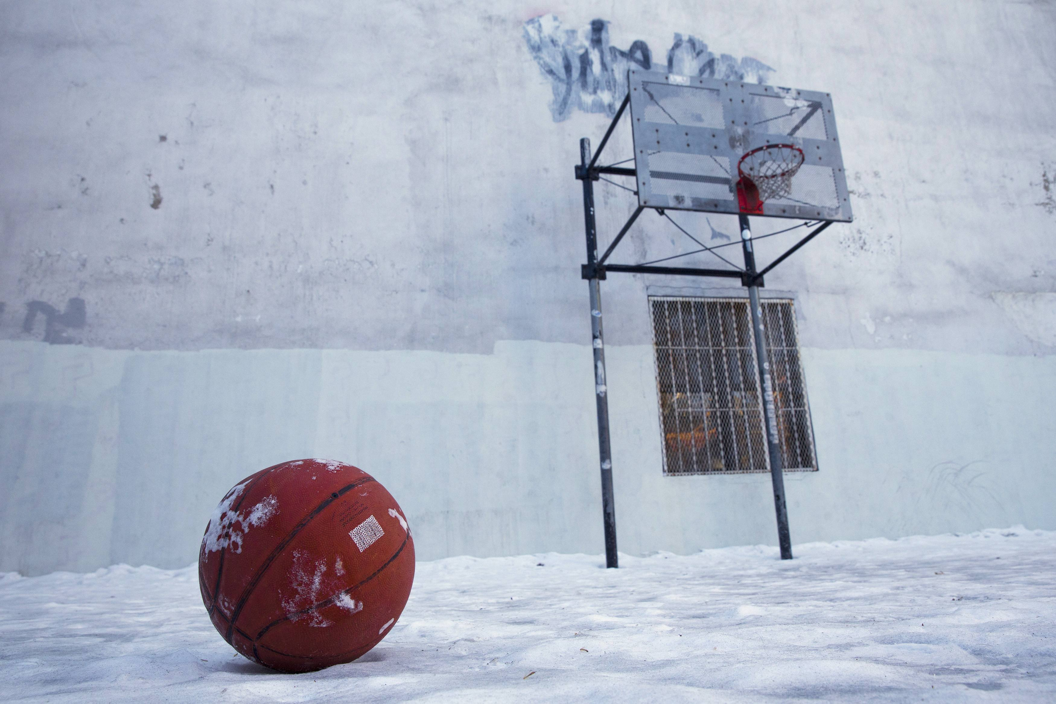 Basketball sits on a frozen basketball court in Lower Manhattan, New York