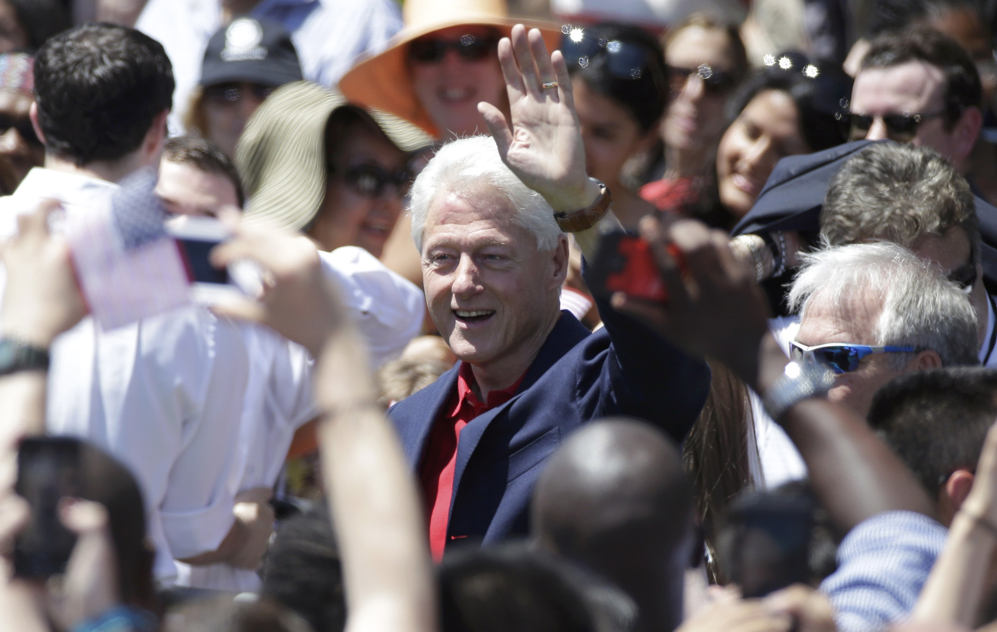 "Former U.S. President Bill Clinton waves as U.S. Democratic presidential candidate Hillary Clinton delivers her ""official launch speech"" at a campaign kick off rally in New York"