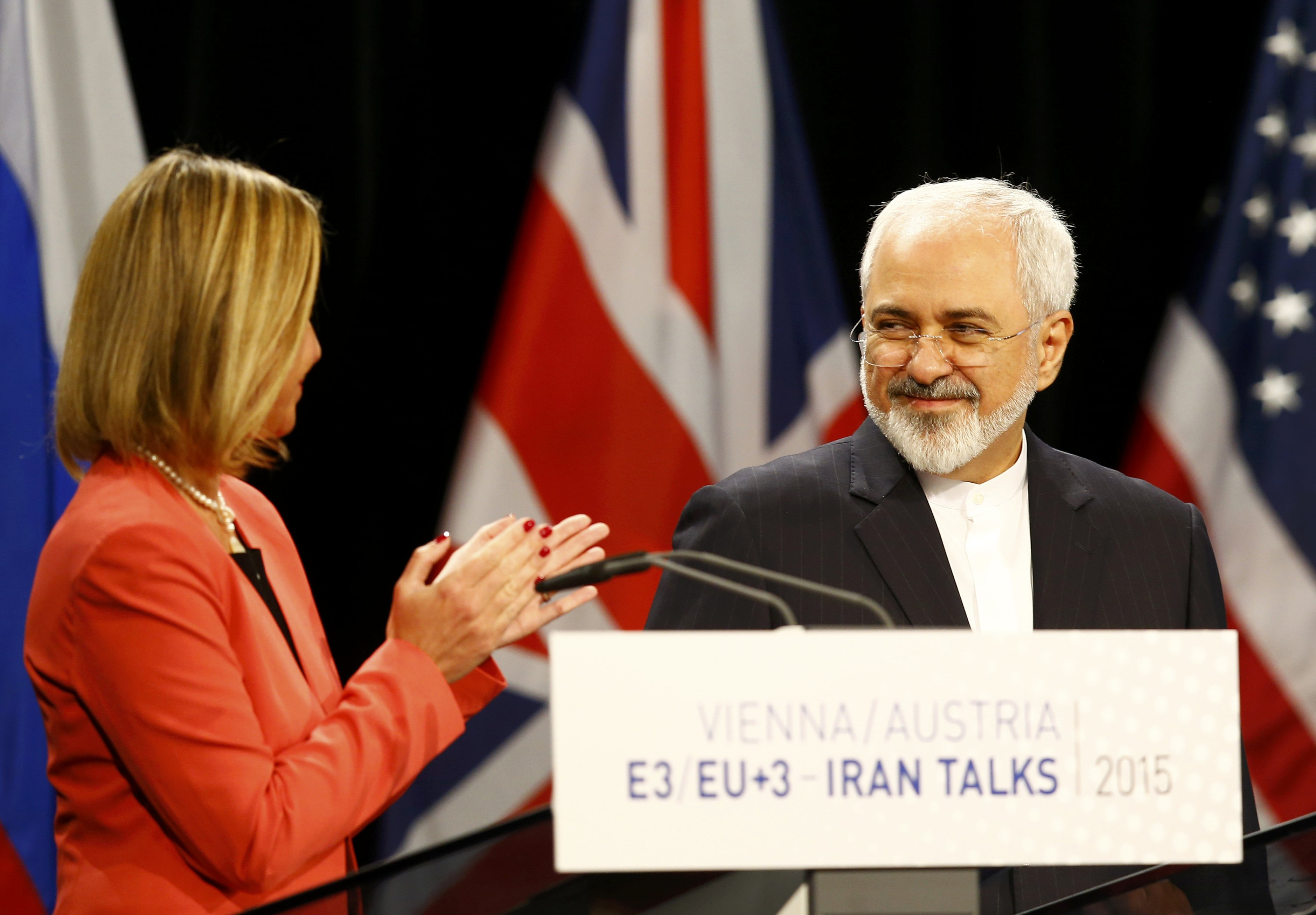 High Representative of the European Union for Foreign Affairs and Security Policy Mogherini applauds Iranian FM Zarif during a joint news conference after a plenary session at the United Nations building in Vienna