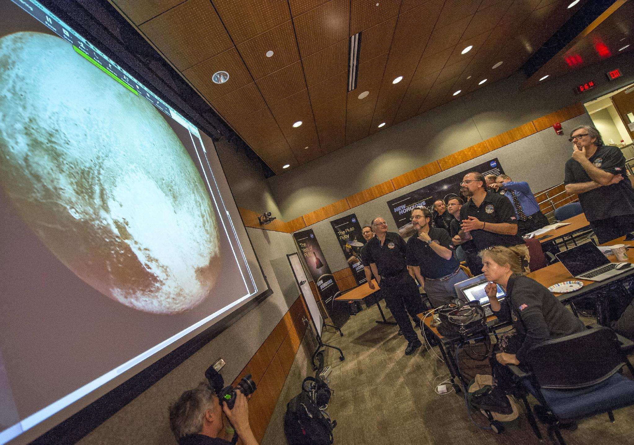 Members of the New Horizons science team react to seeing the spacecraft's last and sharpest image of Pluto before closest approach later in the day at the Johns Hopkins University Applied Physics Laboratory (APL) in Laurel