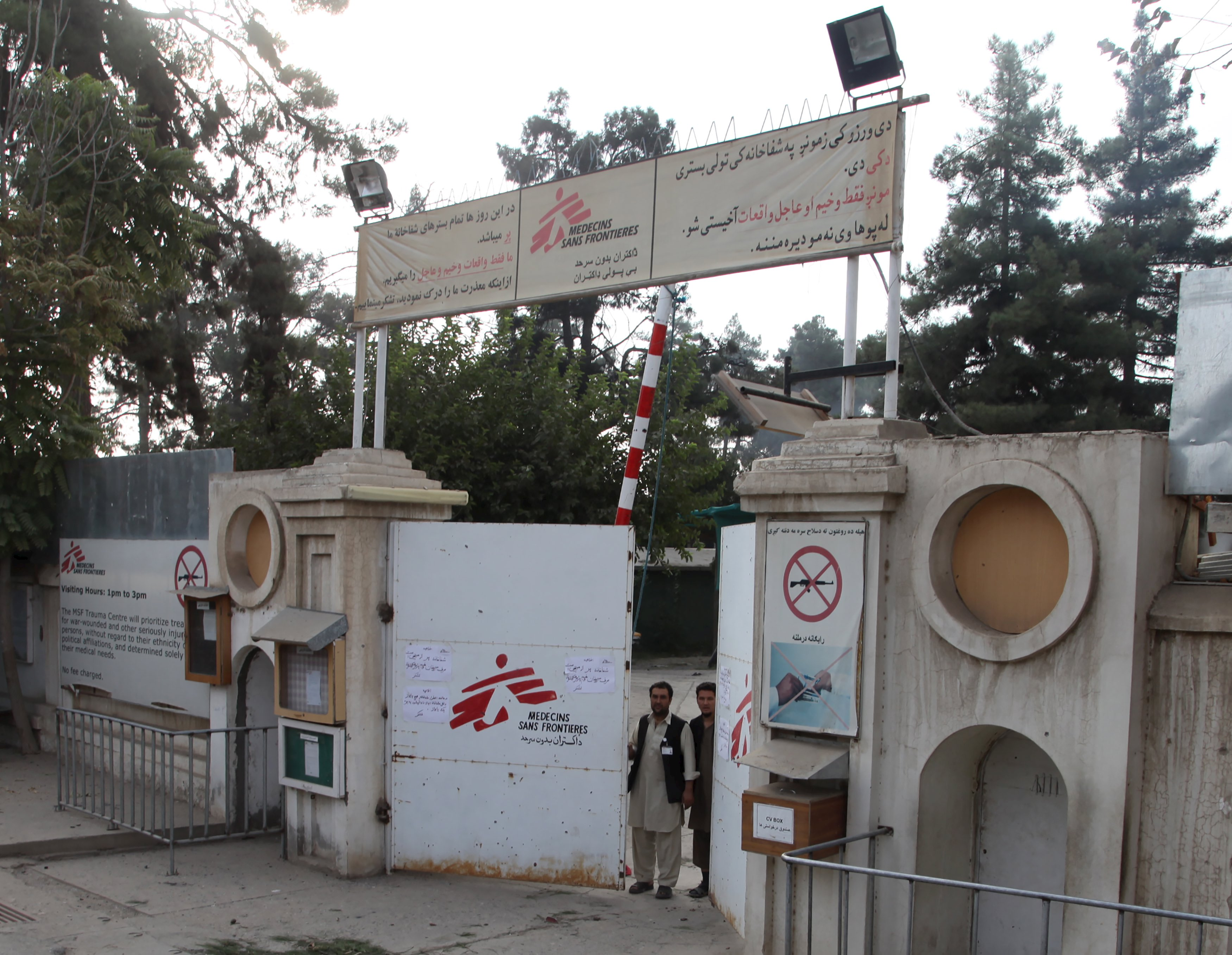 Afghan guards stand at the gate of MSF hospital after an air strike in the city of Kunduz