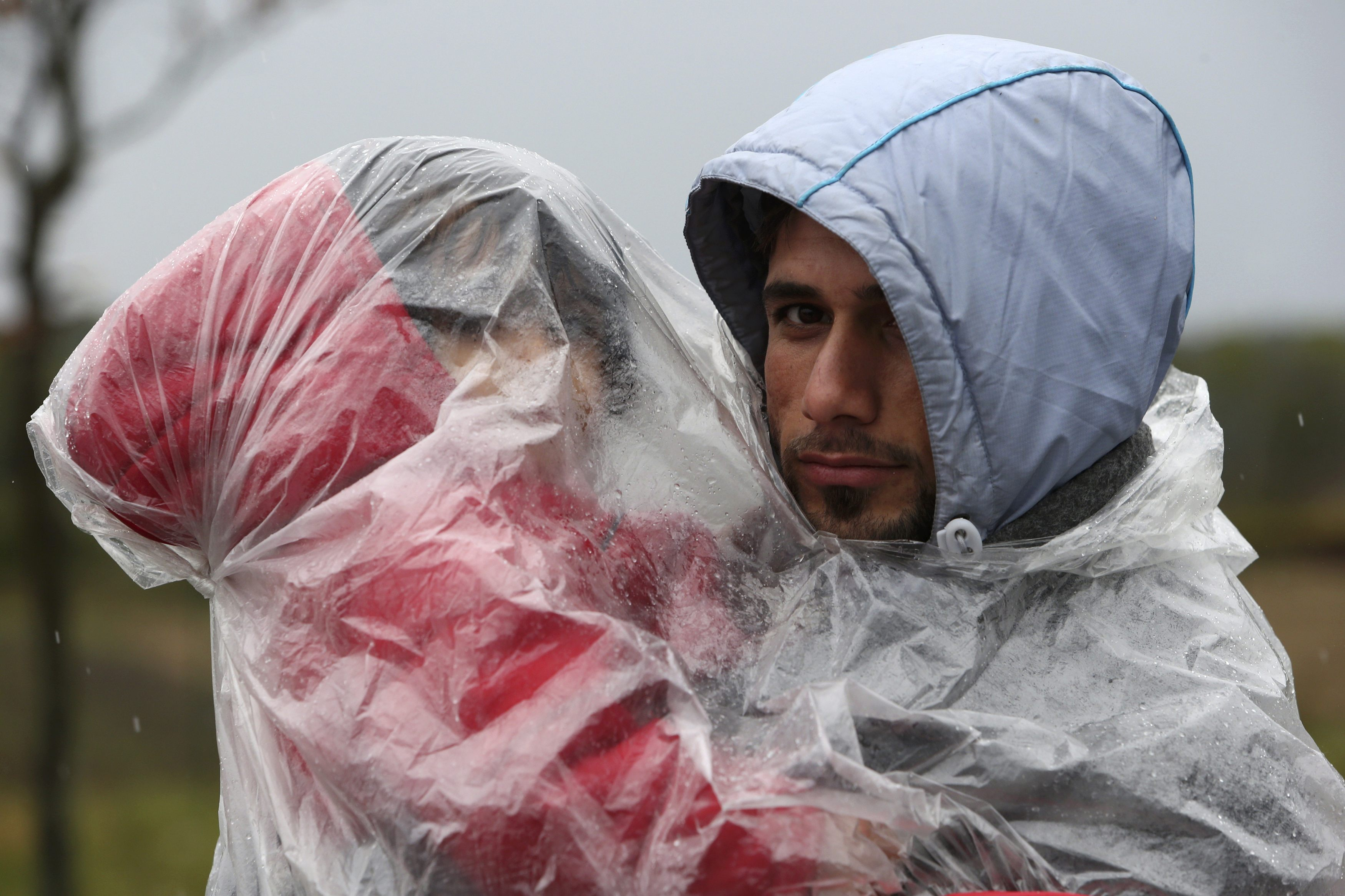 A migrant holds a child as they walk to enter Slovenia from Trnovec