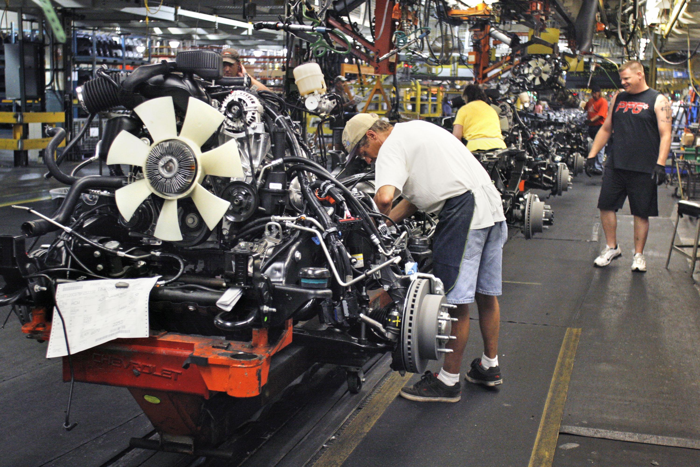 Workers assemble trucks on the General Motors assembly line in Flint, Michigan - AFP Photo/Bill Pugli