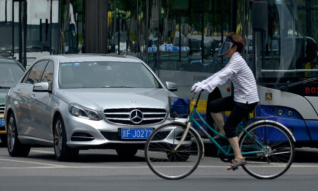 A woman rides her bicycle past a Mercedes Benz at a cross roads in Beijing on August 5, 2014