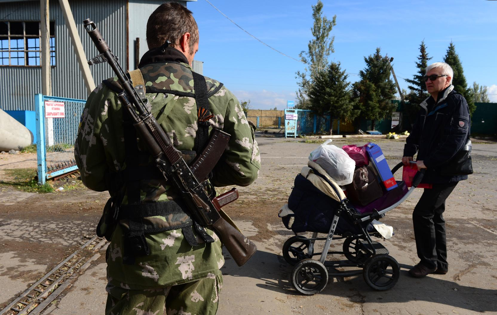 A man pushing goods in a baby carriage crosses the border from Russia to Ukraine at the Uspenka border post, on September 26, 2014.